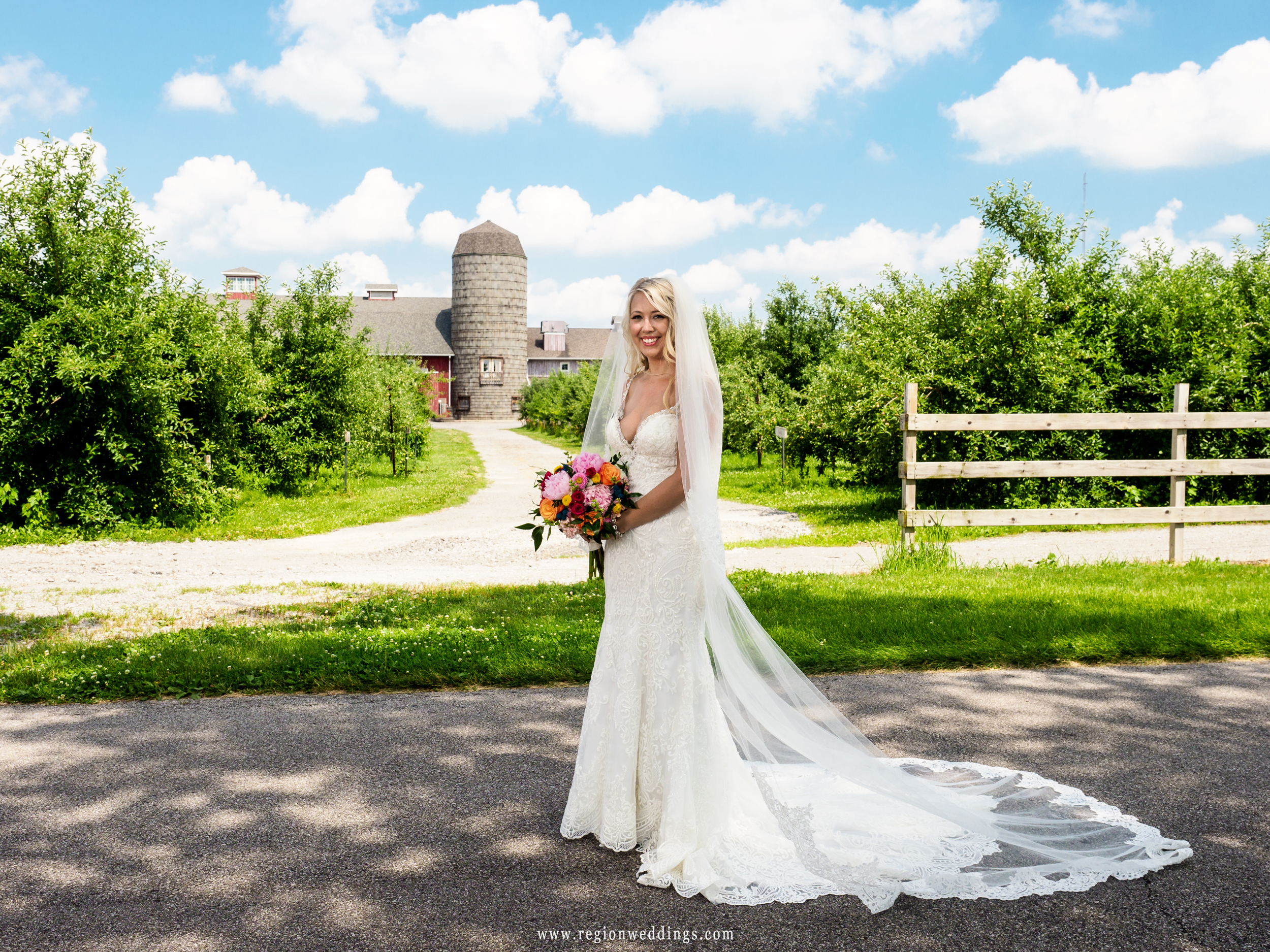 A beautiful bride shows off her dress with the County Line Orchard grain silo in the background.