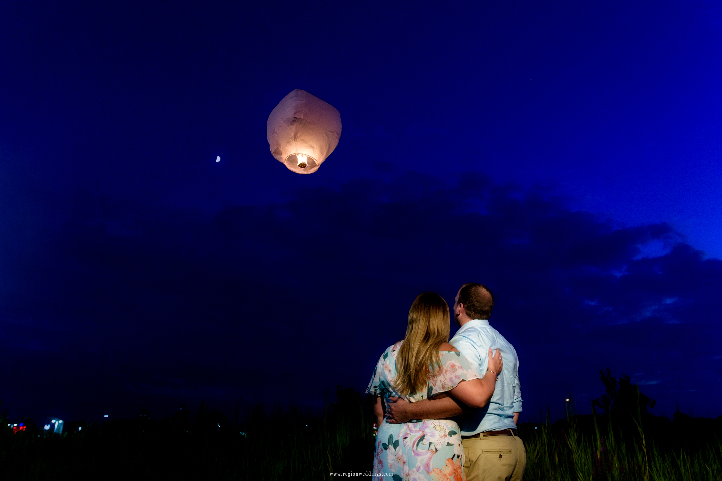 Watching a sky lantern drift off into the night sky for a twilight engagement photo.