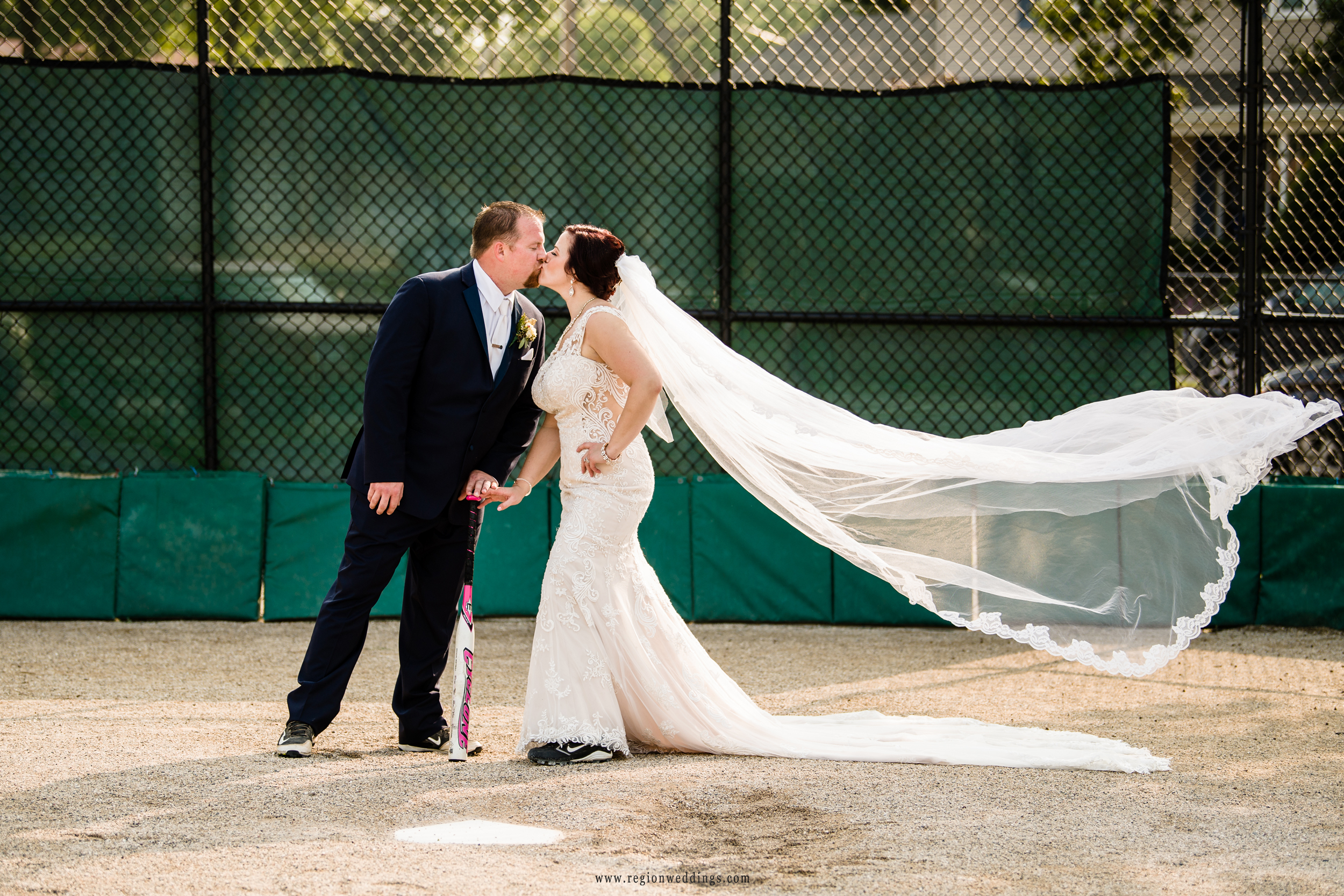 The bride's veil flies in the wind as she kisses her groom at home plate.