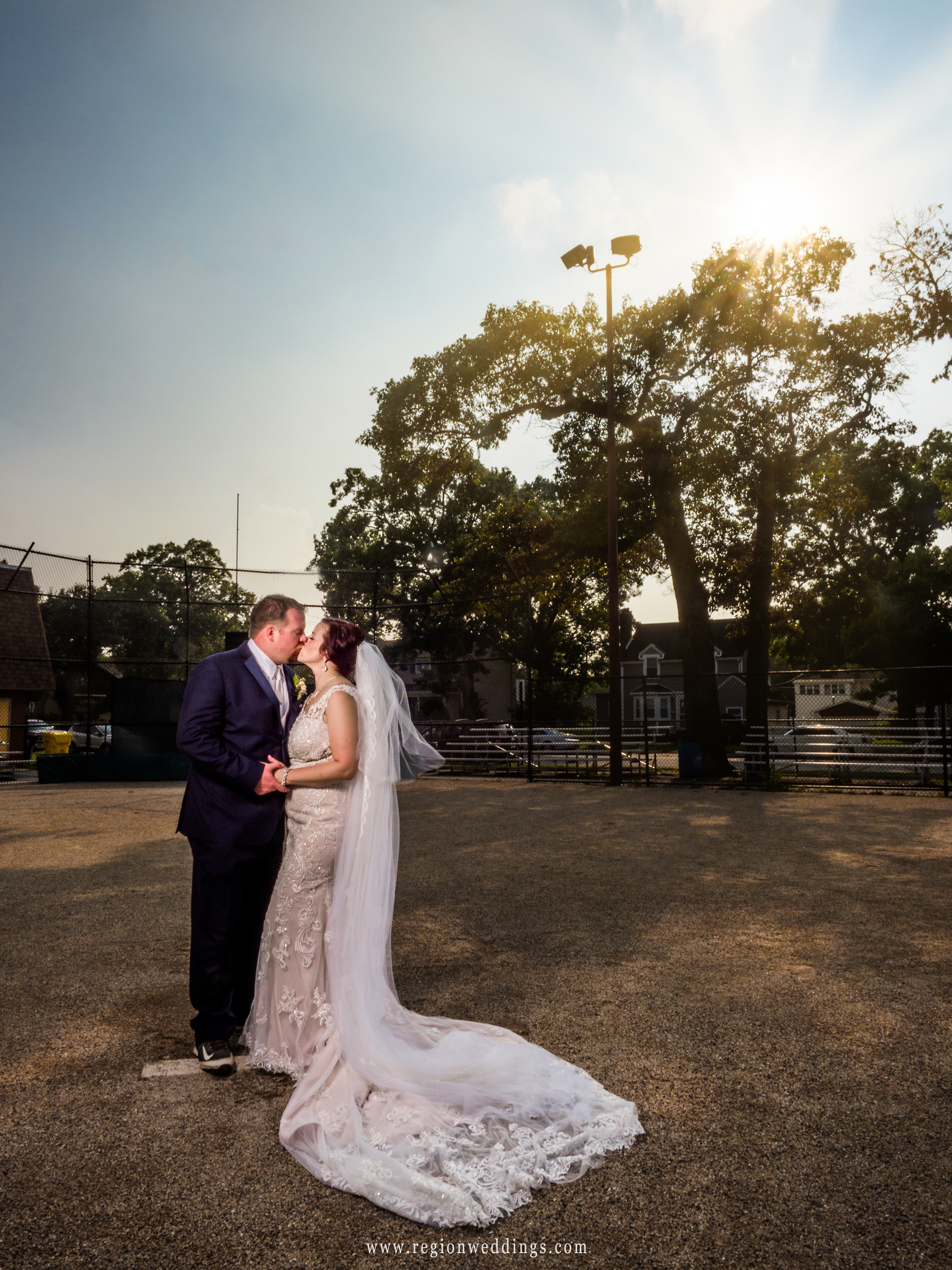 Bride and groom share a kiss on the pitcher's mound.