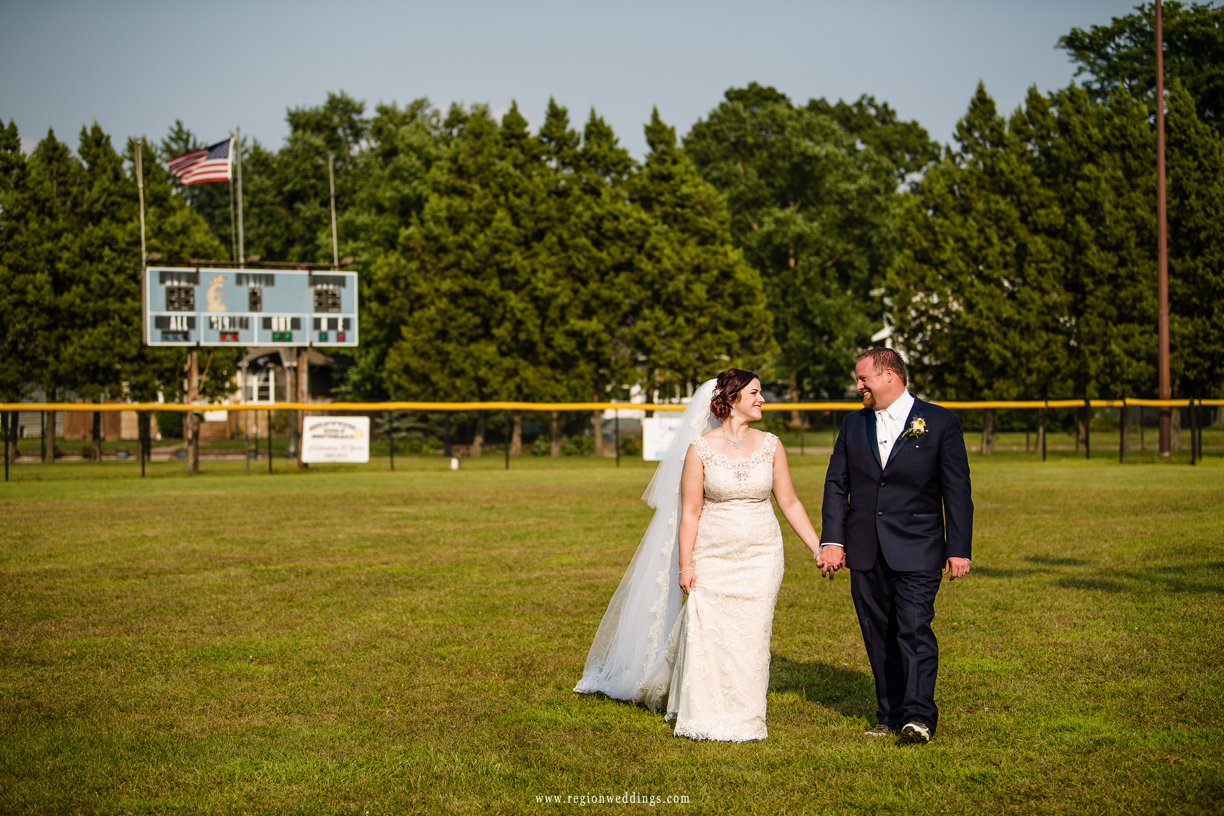 Bride and groom take a stroll in the outfield of the baseball field.