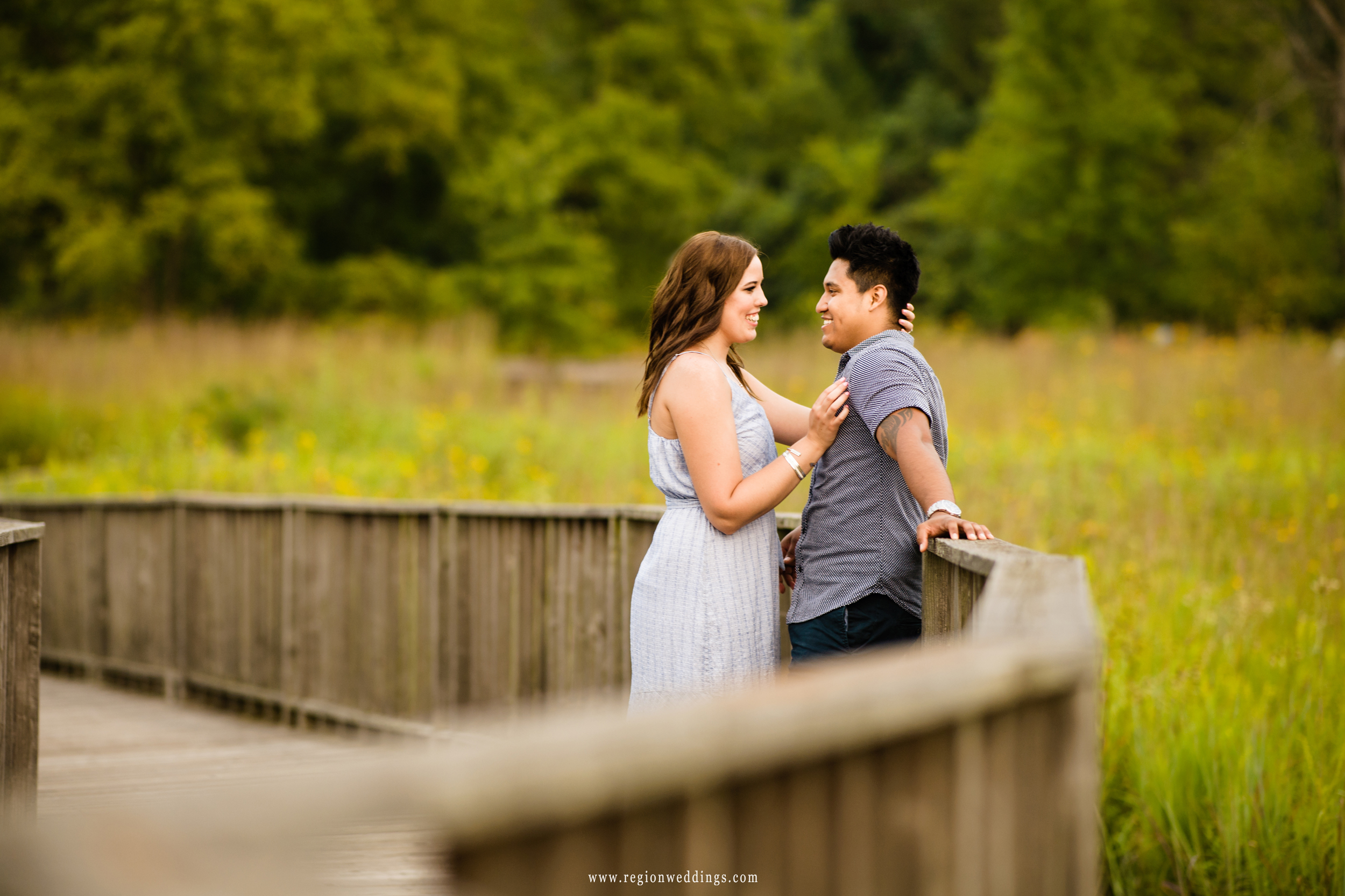 A young couple embraces on the wooden boardwalk at Coffee Creek.
