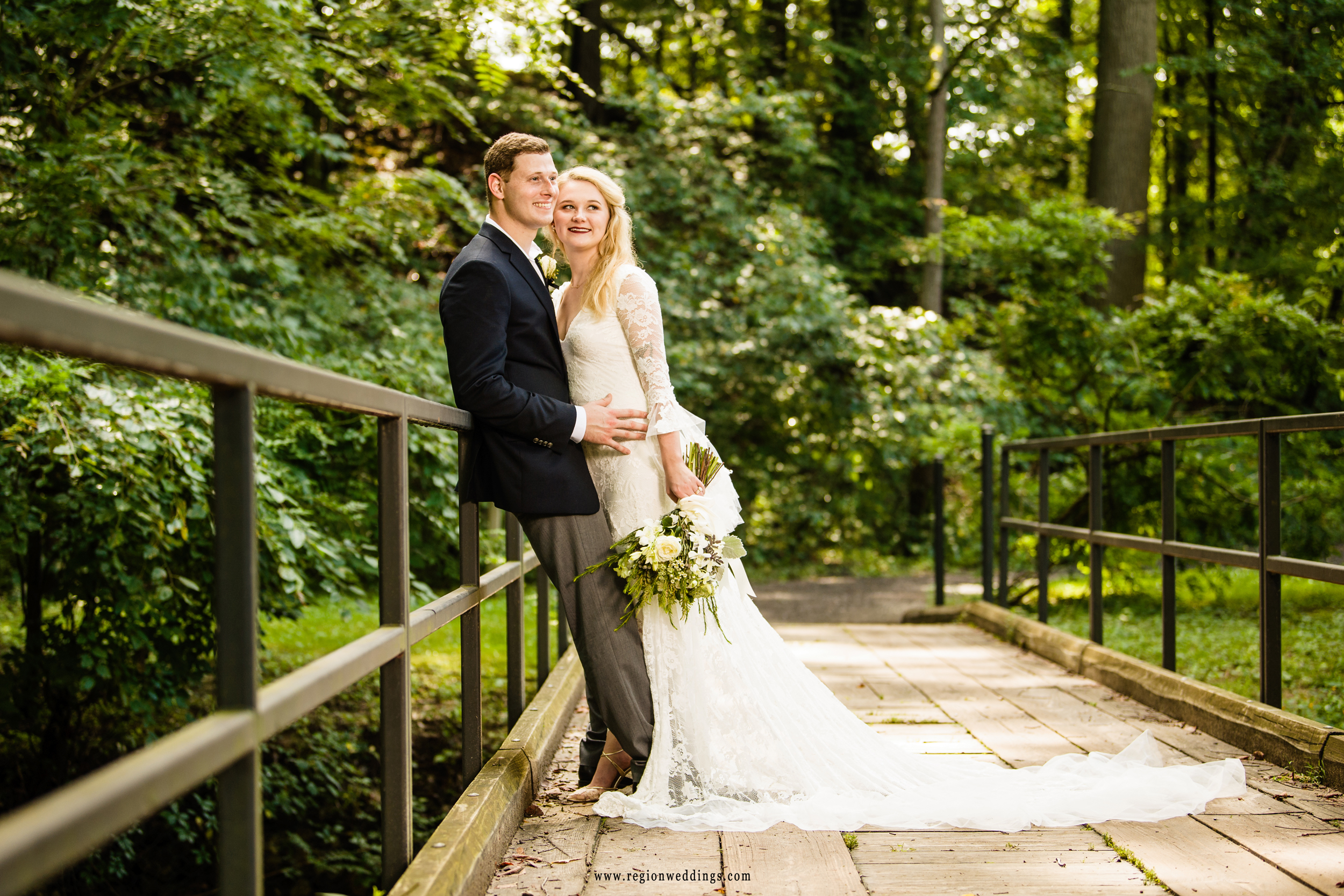 Bride and groom gaze off into the distance on a rustic bridge.