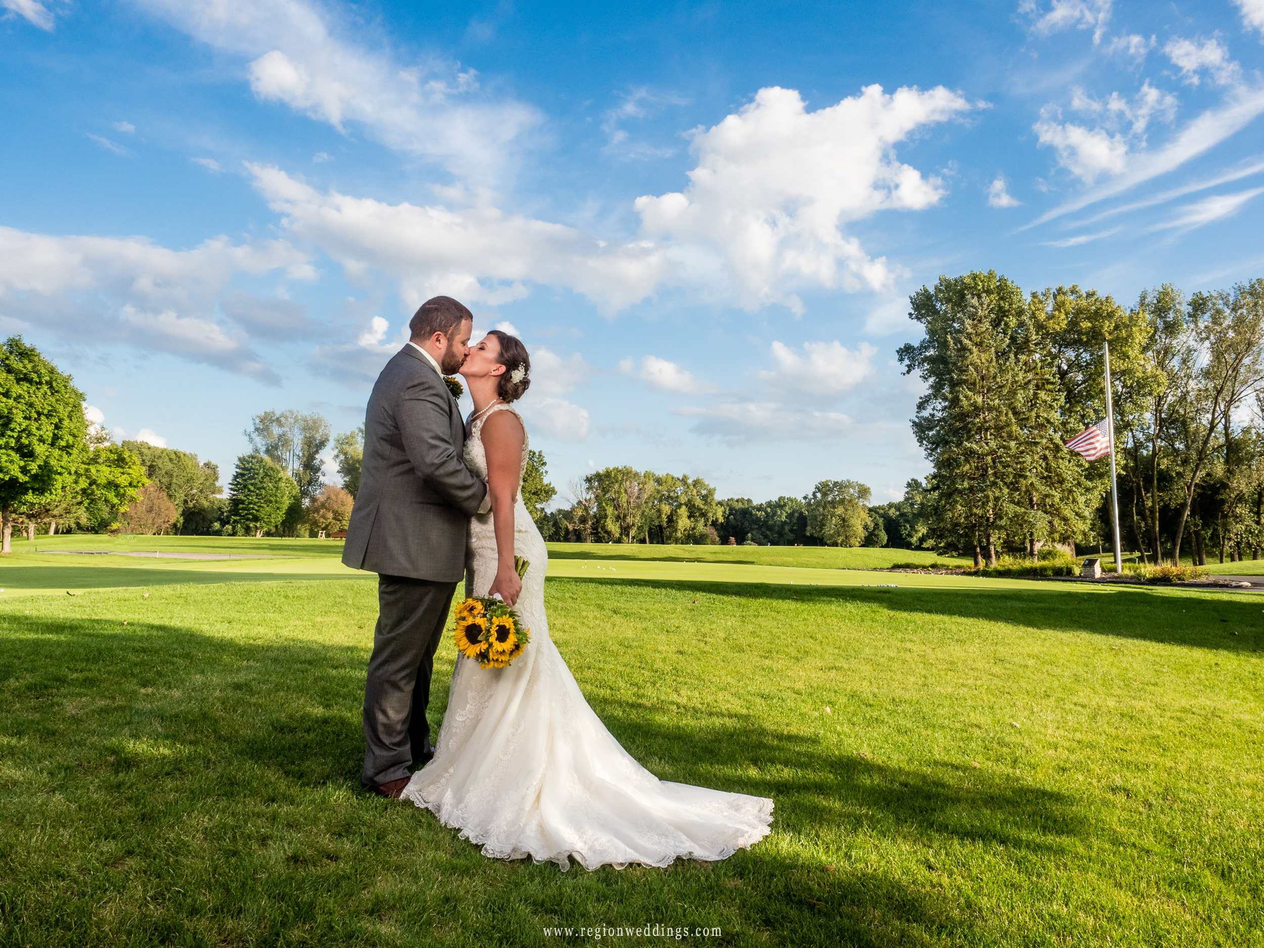 Kiss on the golf course under a beautiful blue sky.