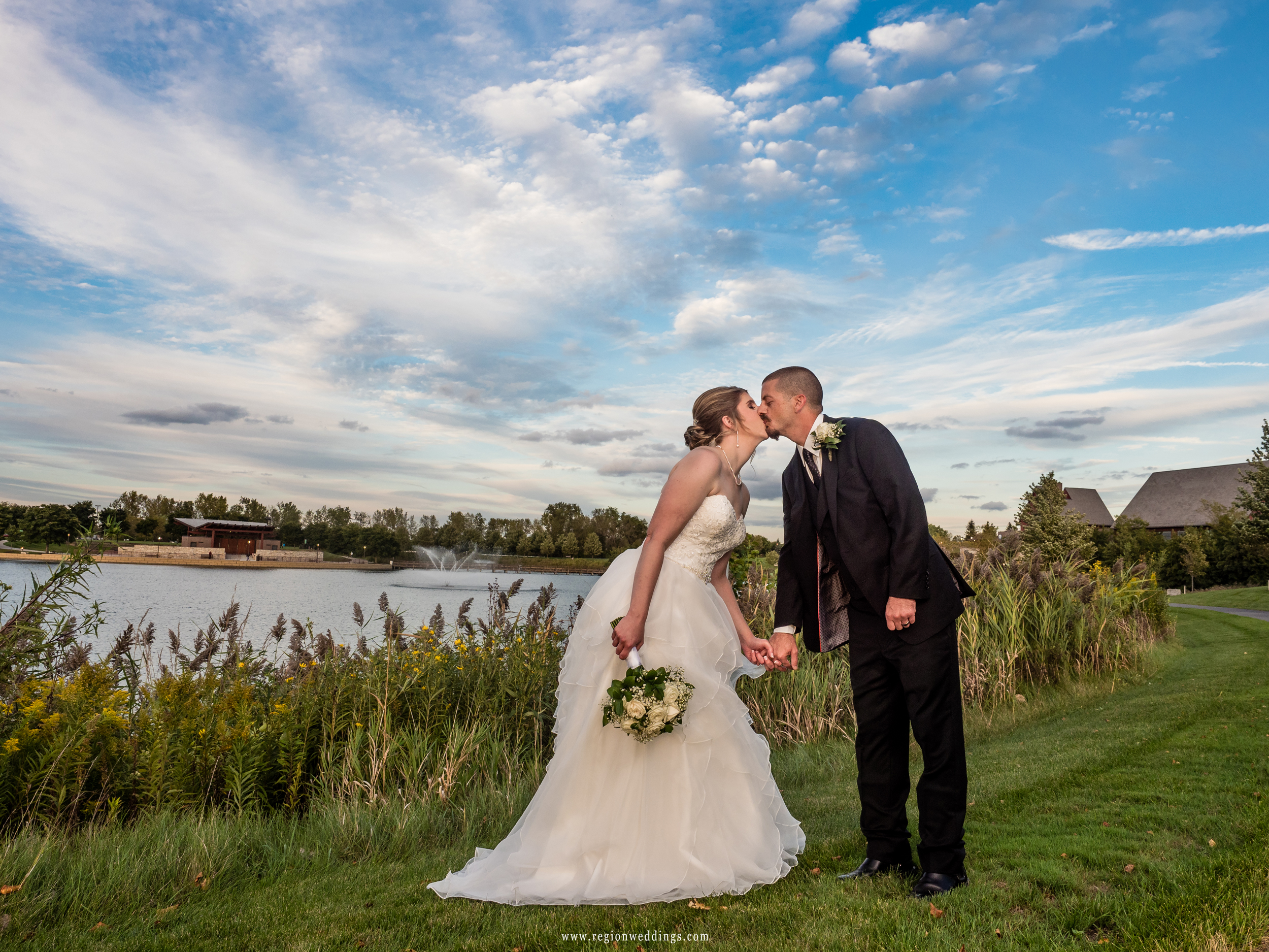 Bride and groom kiss under deep blue skies at Centennial park.