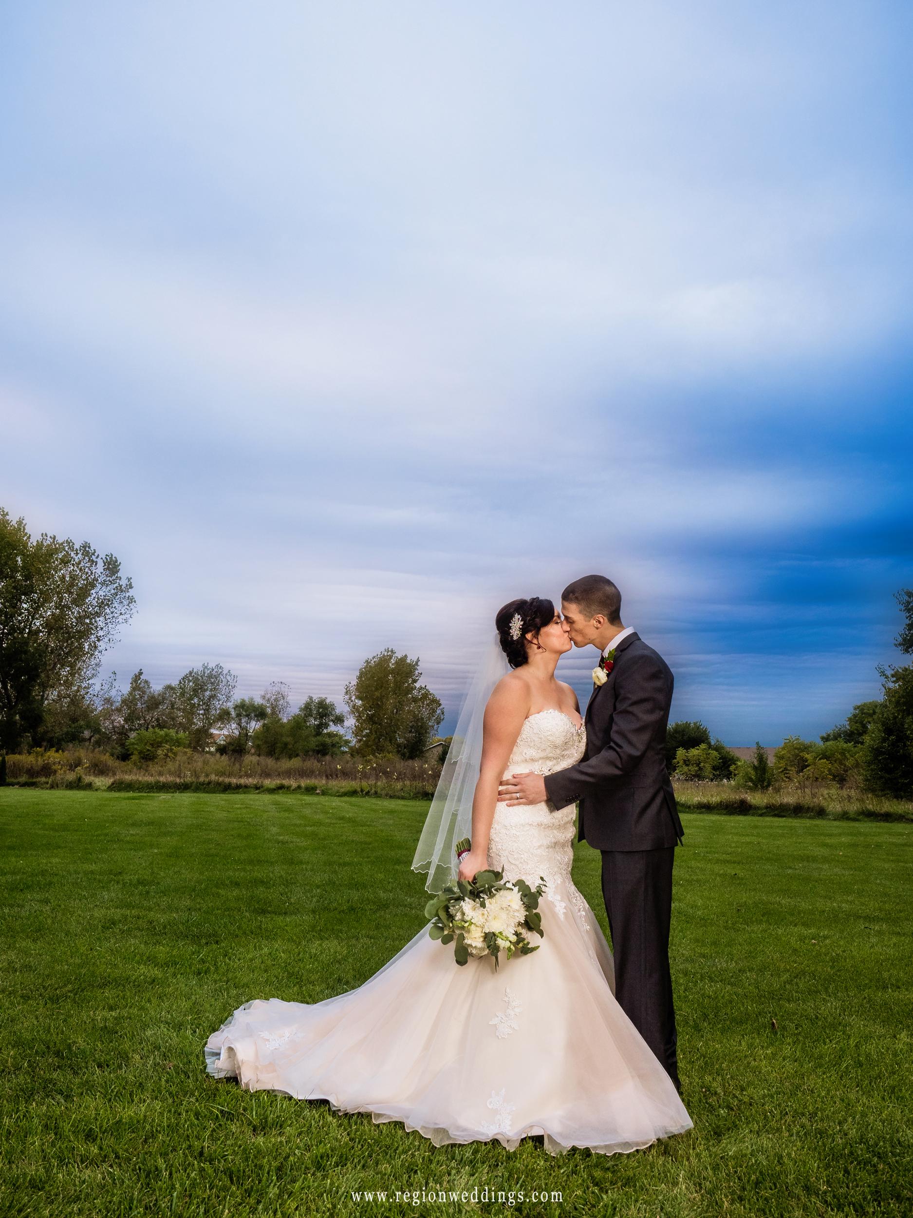 Bride and groom kiss beneath a blue sky.