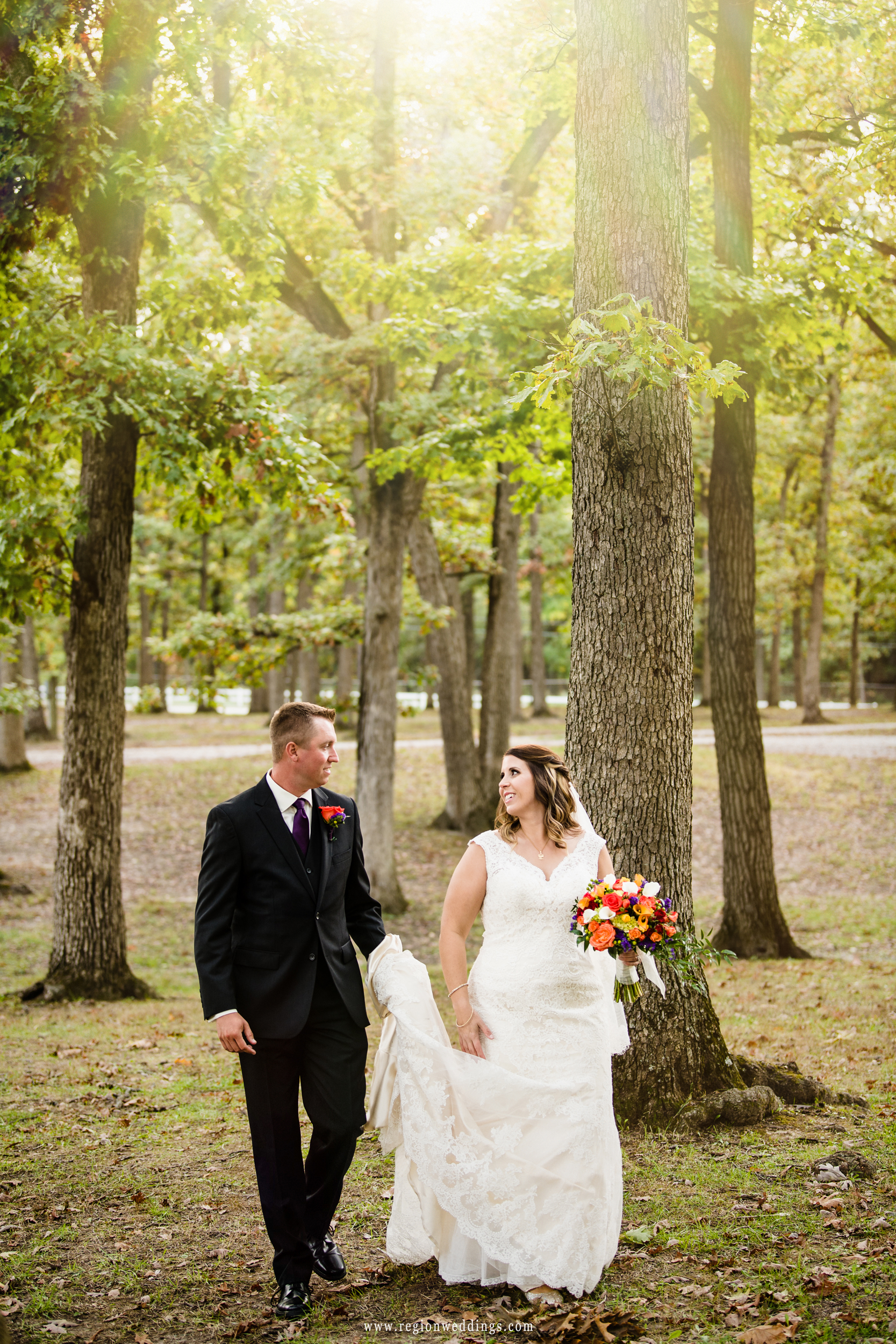 The bride and groom take a stroll in the wood at Lake County Fairgrounds.