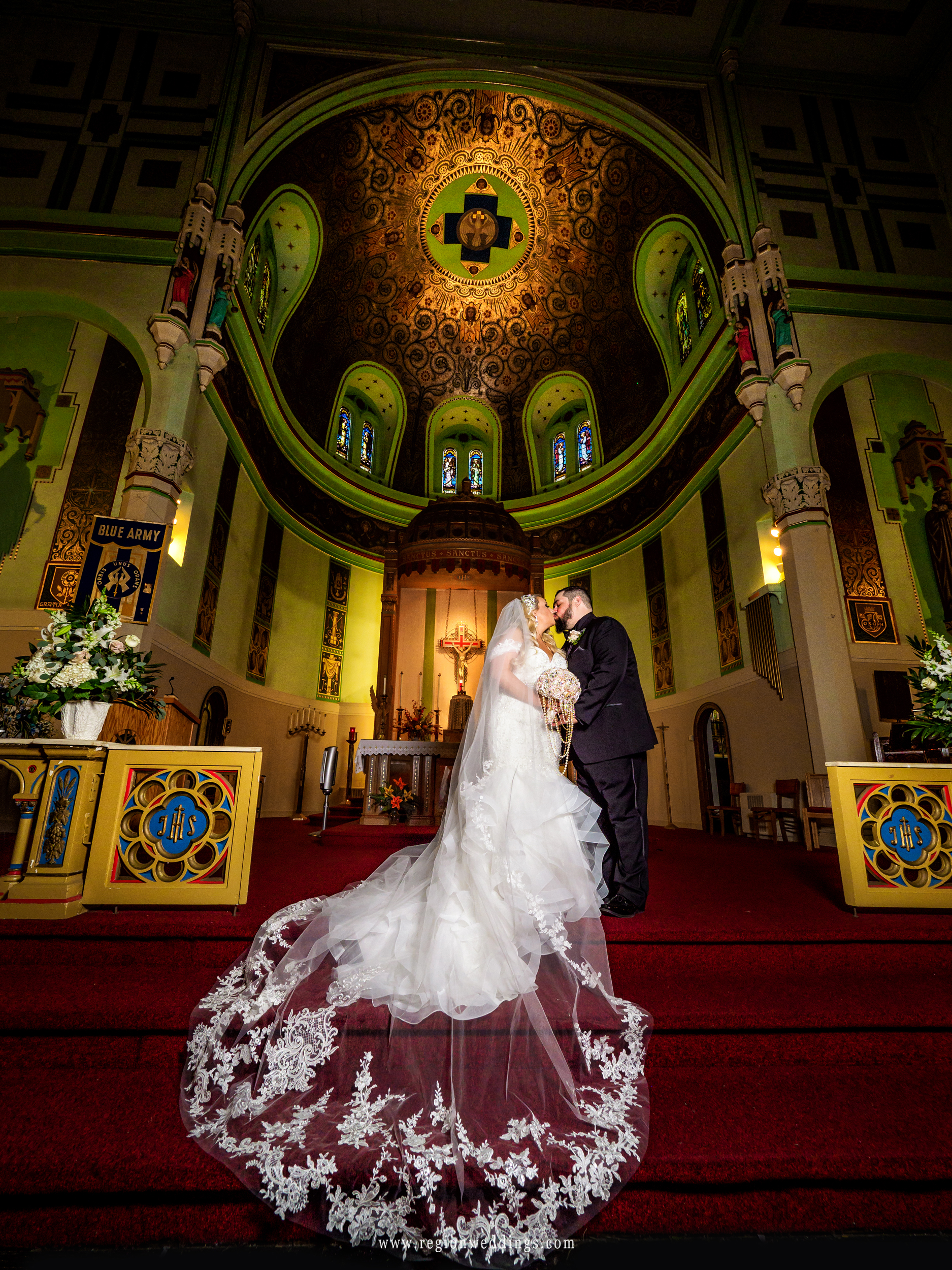 Bride and groom kiss on the altar at St. Stanislaus Church in Michigan City, Indiana.