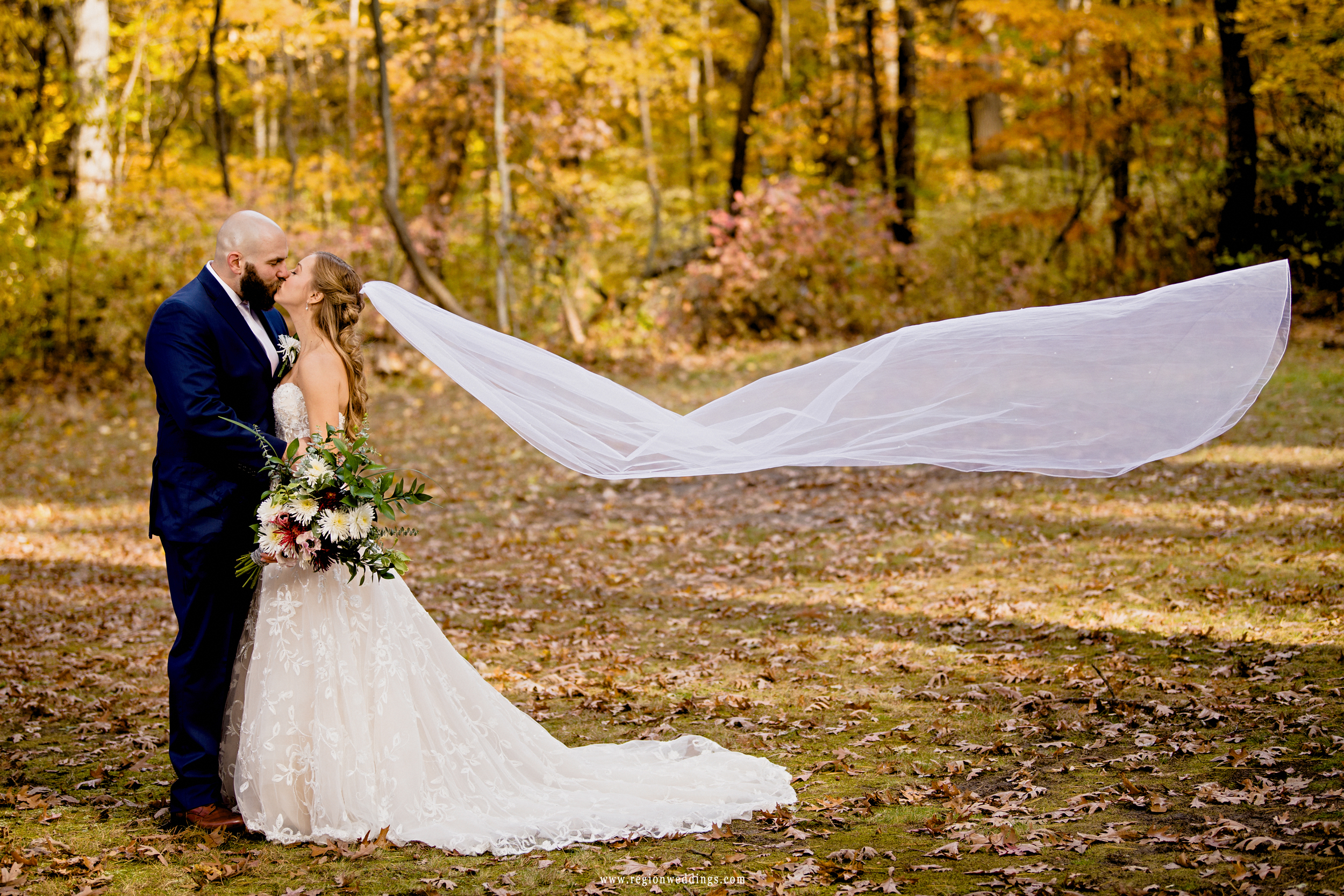 The bride's long veil flows into the air as her groom kisses her.