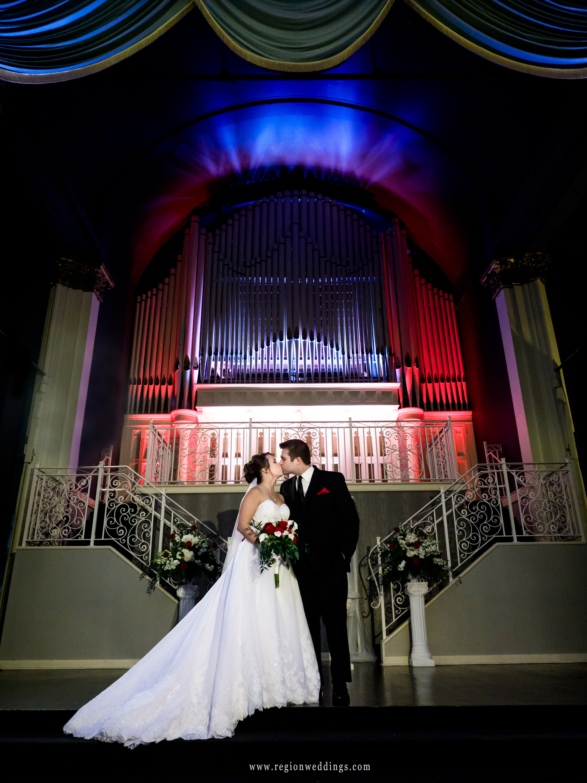 Bride and groom kiss center stage at The Uptown Center.