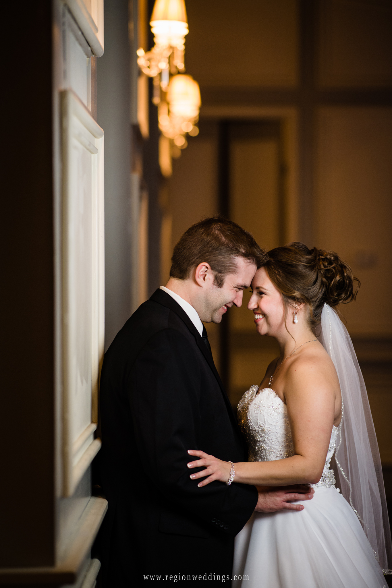 Bride and groom embrace inside the ballroom of Uptown Center for Performing Arts.
