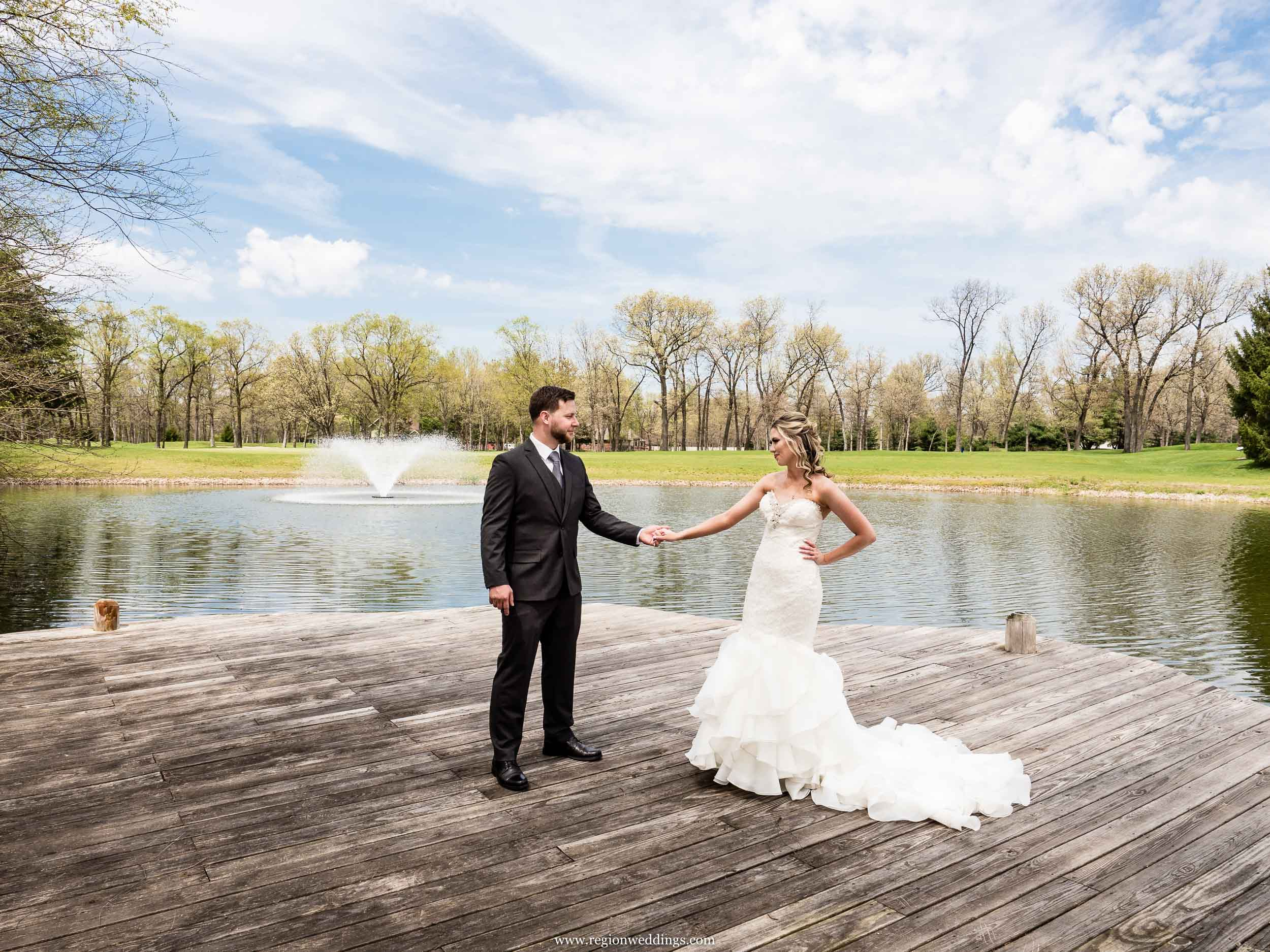 Bride and groom hold hands on the lake pier at Sandy Pines Golf Course.