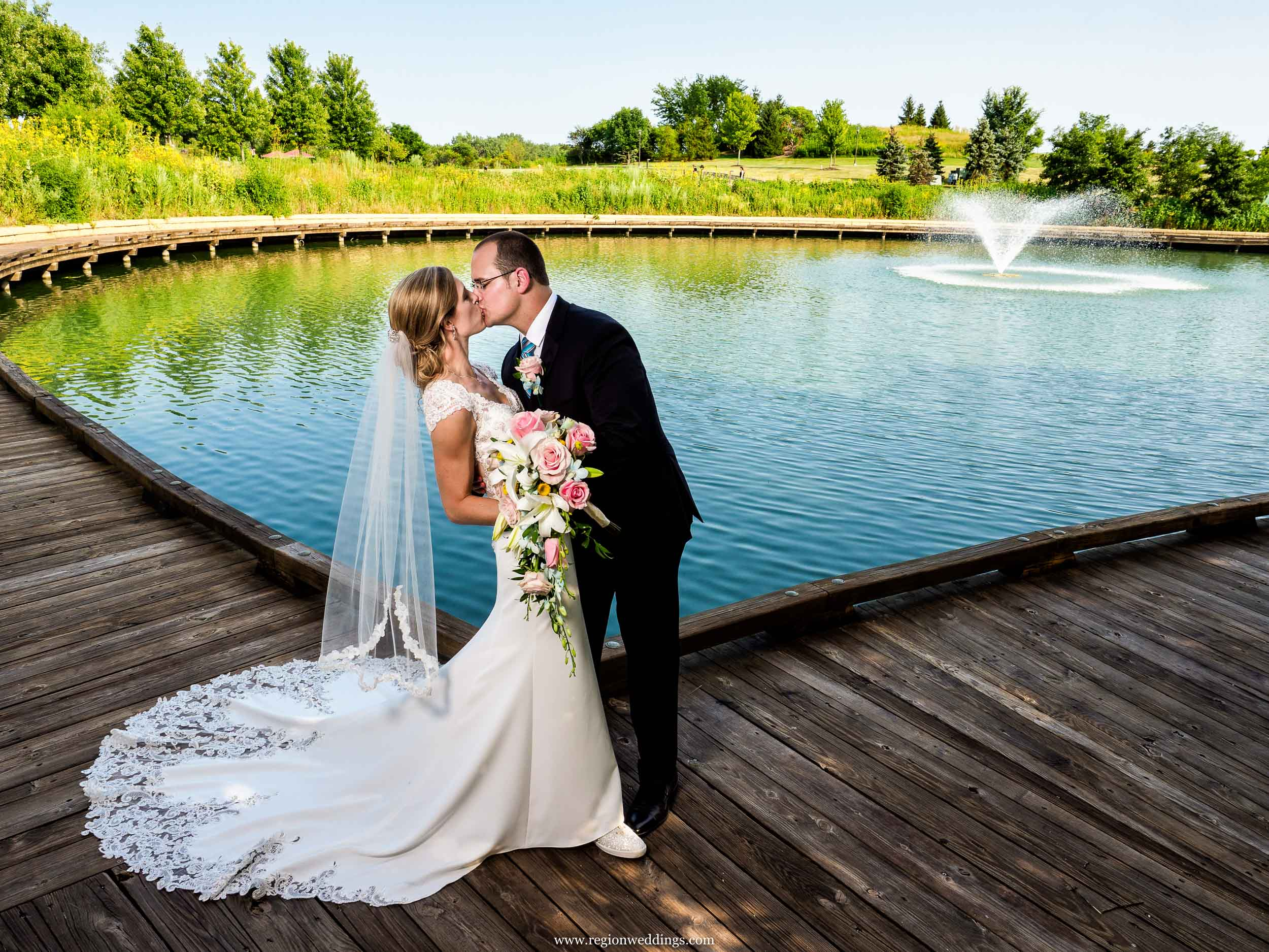 The groom kisses the bride at the edge of the Centennial Park Lake.