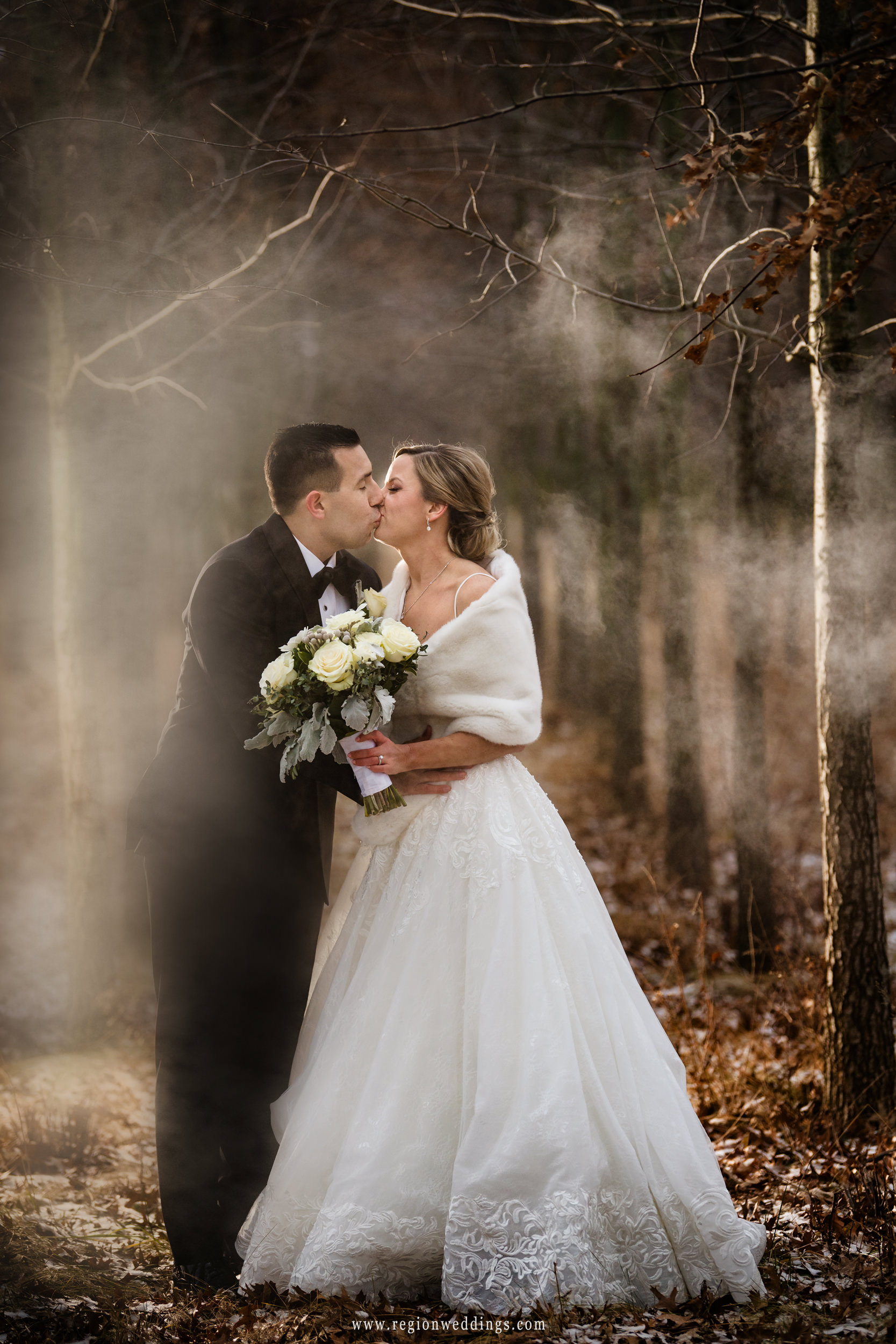 Fog surrounds the bride and groom in this outdoor winter wedding photo.