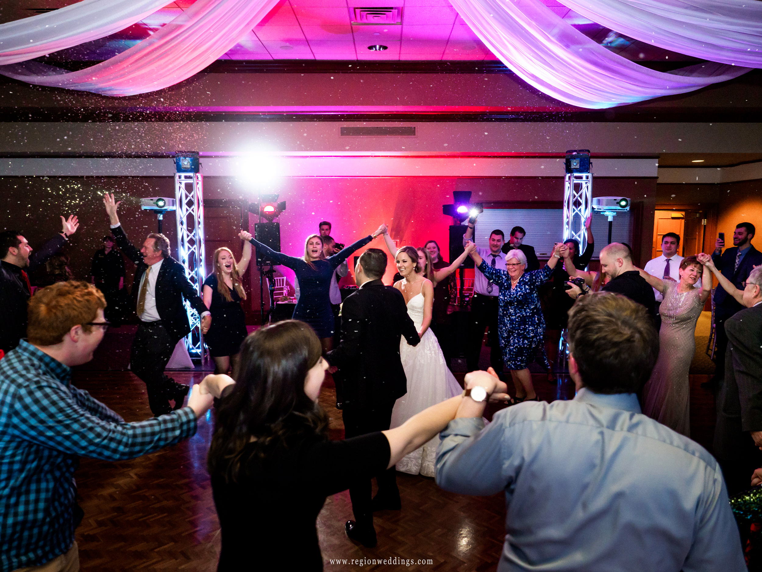 Snow falls on the dance floor at a winter wedding reception at Sand Creek Country Club.
