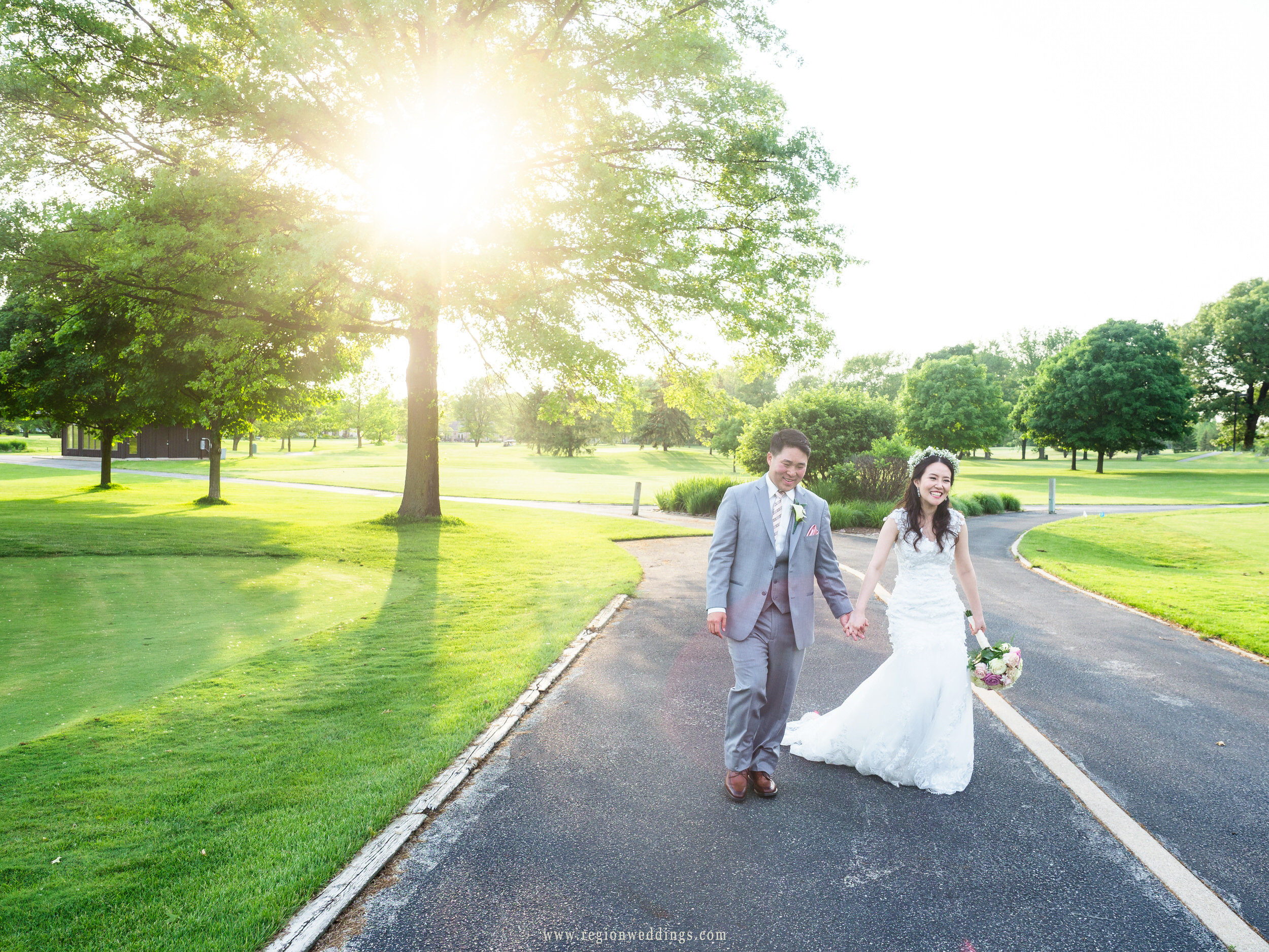 Bride and groom take a stroll in the golden hour sun.