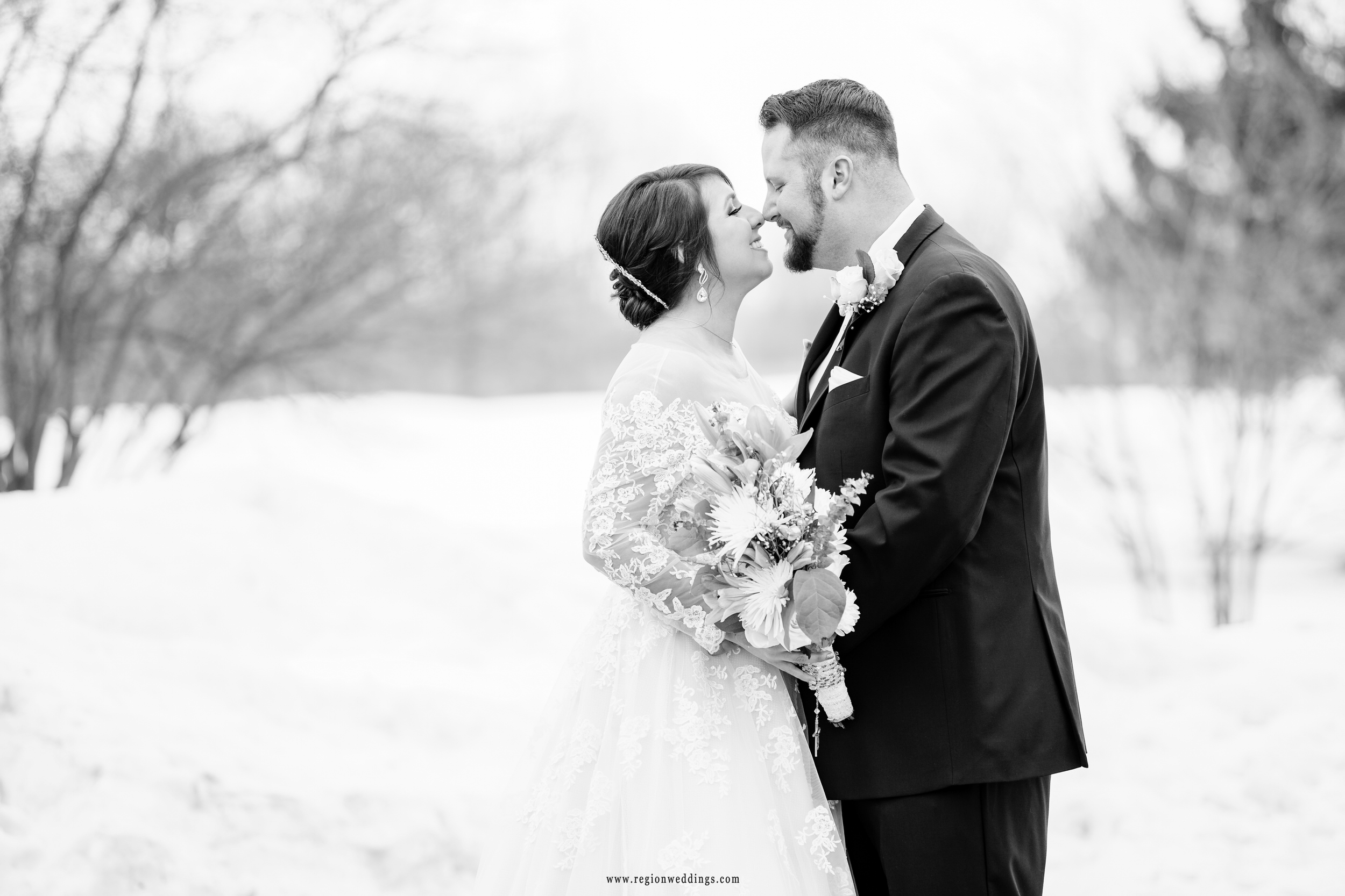 Bride and groom eskimo kiss at their winter wedding in a snow covered field.