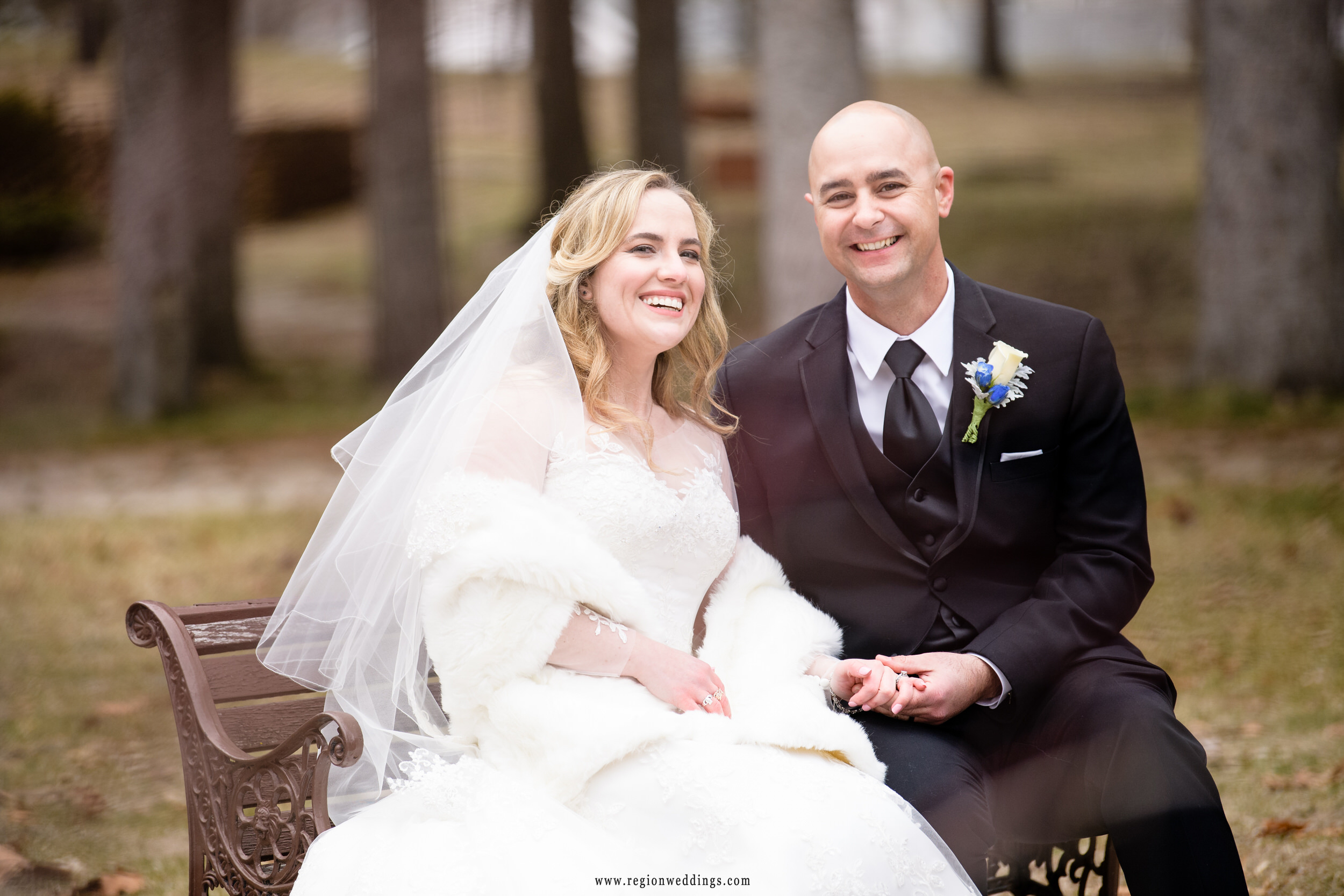 Bride and groom on a park bench at Carmelite Shrine during their winter wedding.