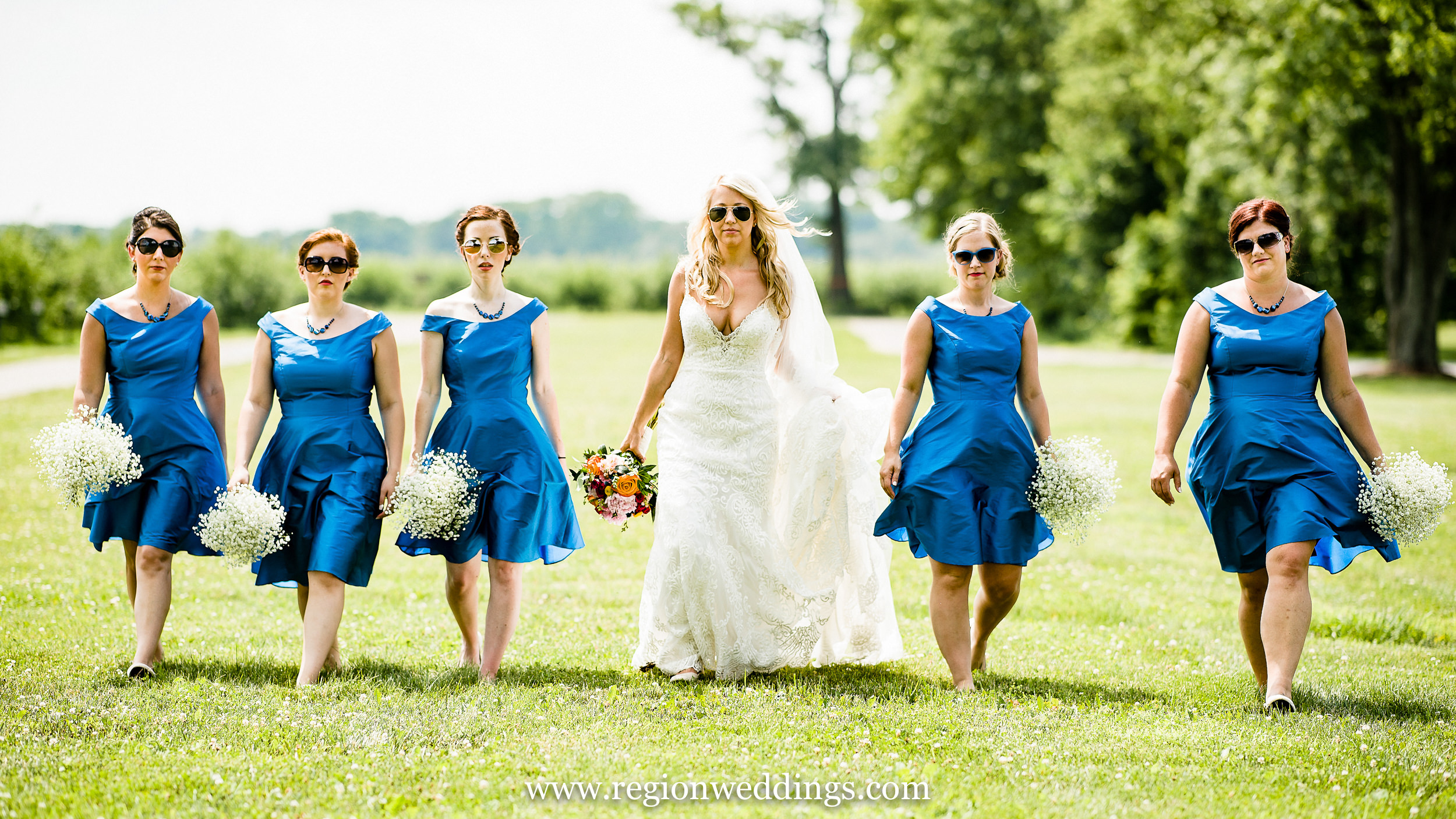 A gang of bridesmaids rushes toward the camera at County Line Orchard.
