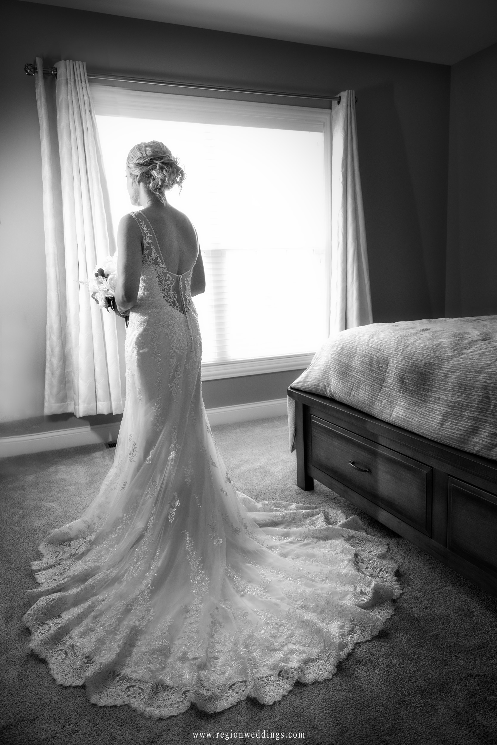The bride stands alone in her bedroom in her wedding dress.