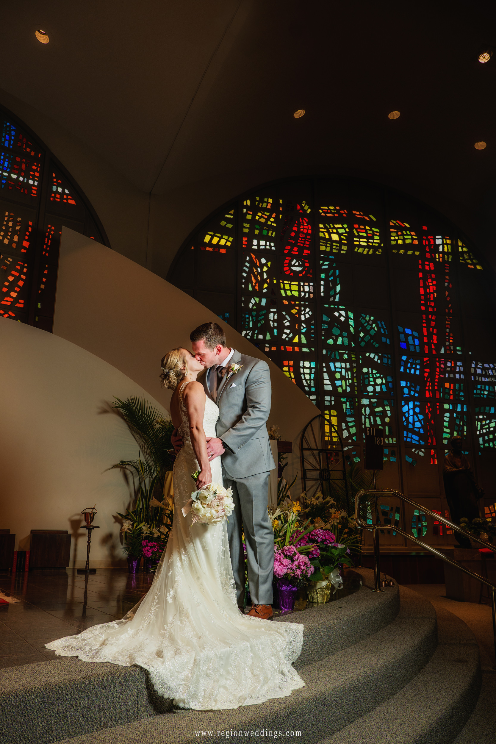 Bride and groom kiss on the altar at Saint Paul Catholic Church in Valparaiso, Indiana.