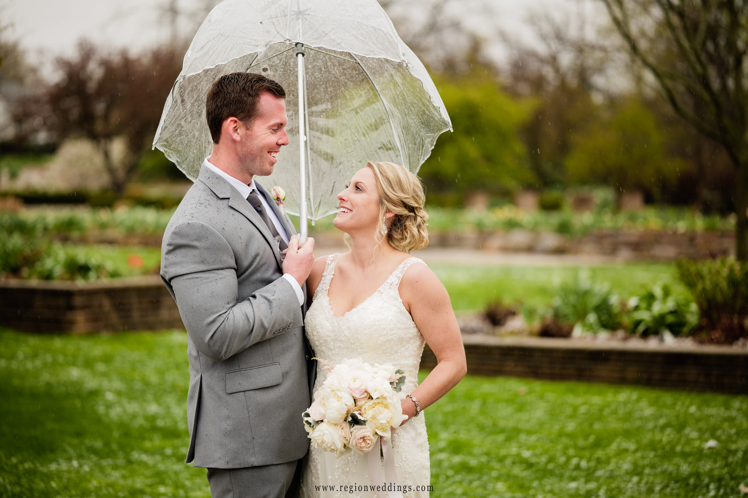 Bride and groom have a laugh in the rain at Ogden Garden.