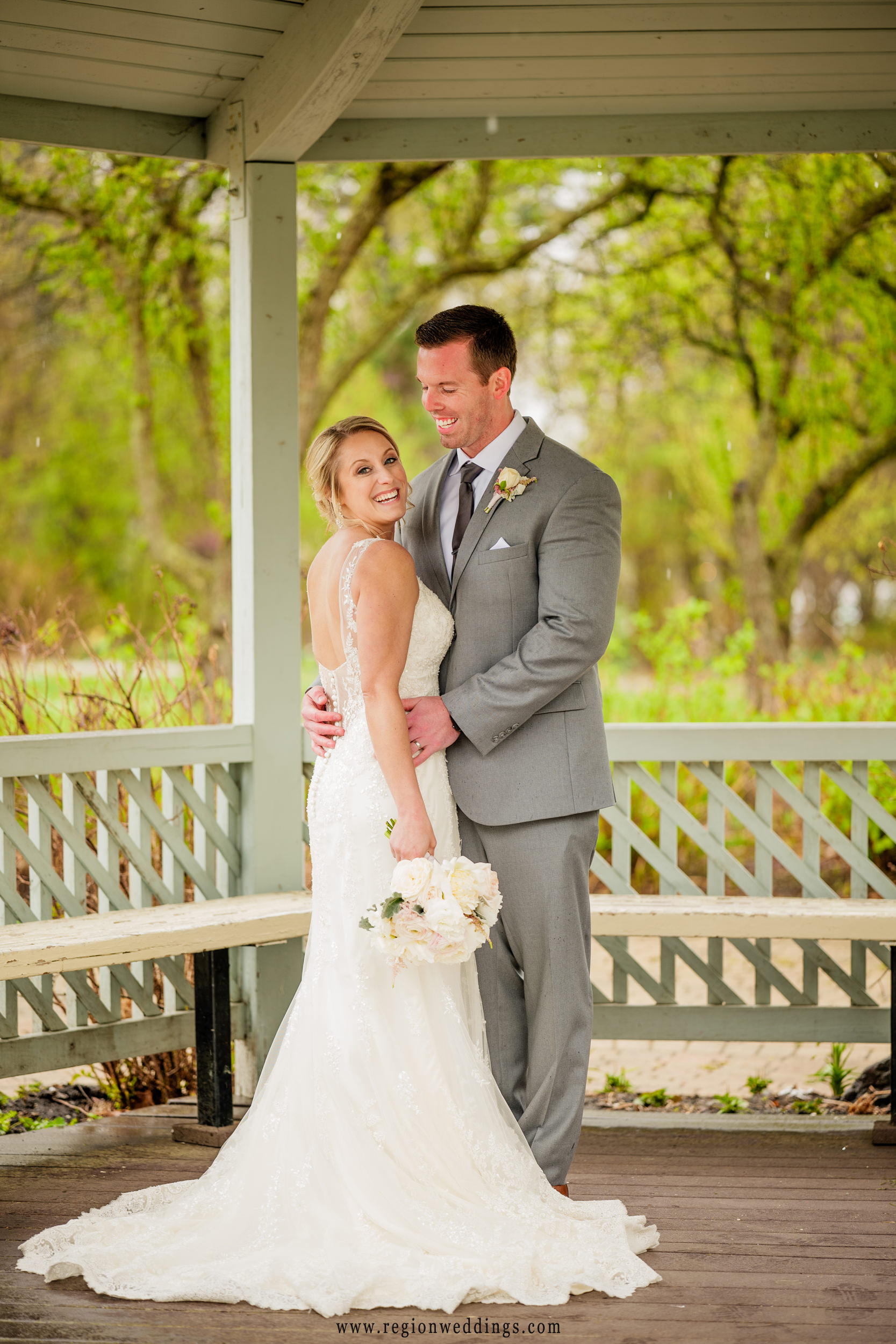 Bride and groom share a laugh underneath the gazebo during their Spring wedding in late April.