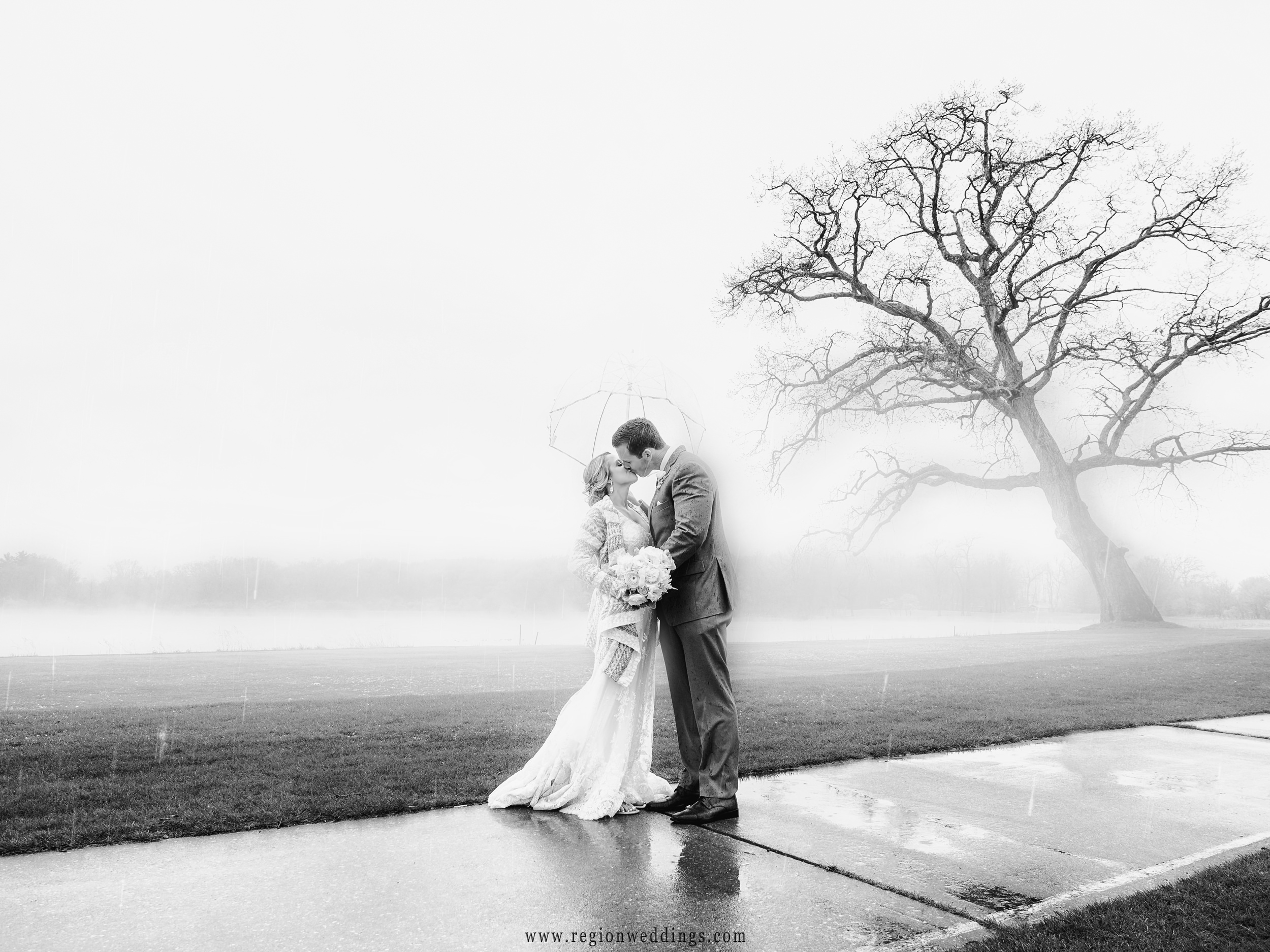 Bride and groom kiss as rain and sleet falls upon them and fog rises over the lake.