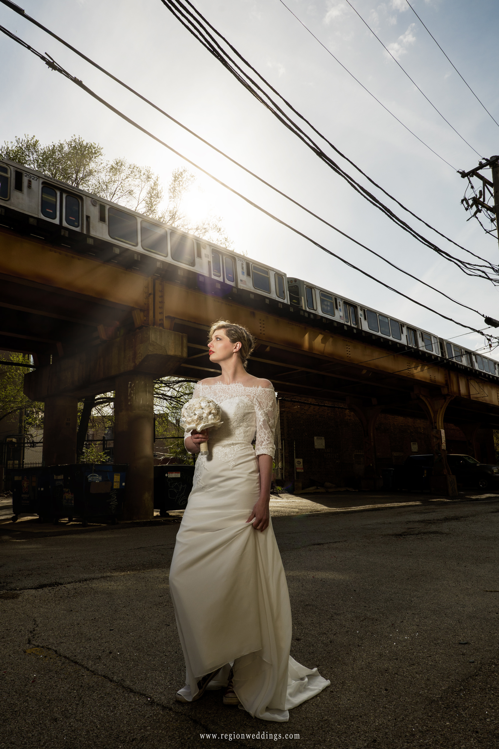 The bride is illuminated by sunlight beneath the L train tracks on the north side of Chicago.