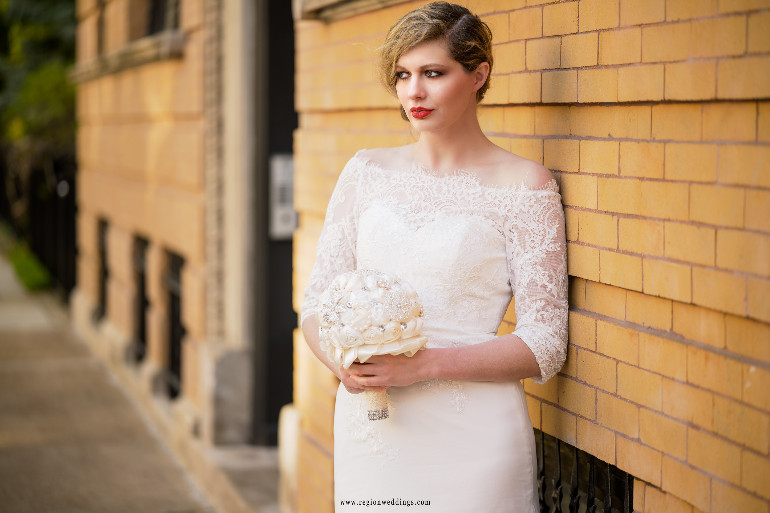 Bride leans against a golden brick wall for her Chicago bridal session in the Bucktown / Wicker Park area of the city.