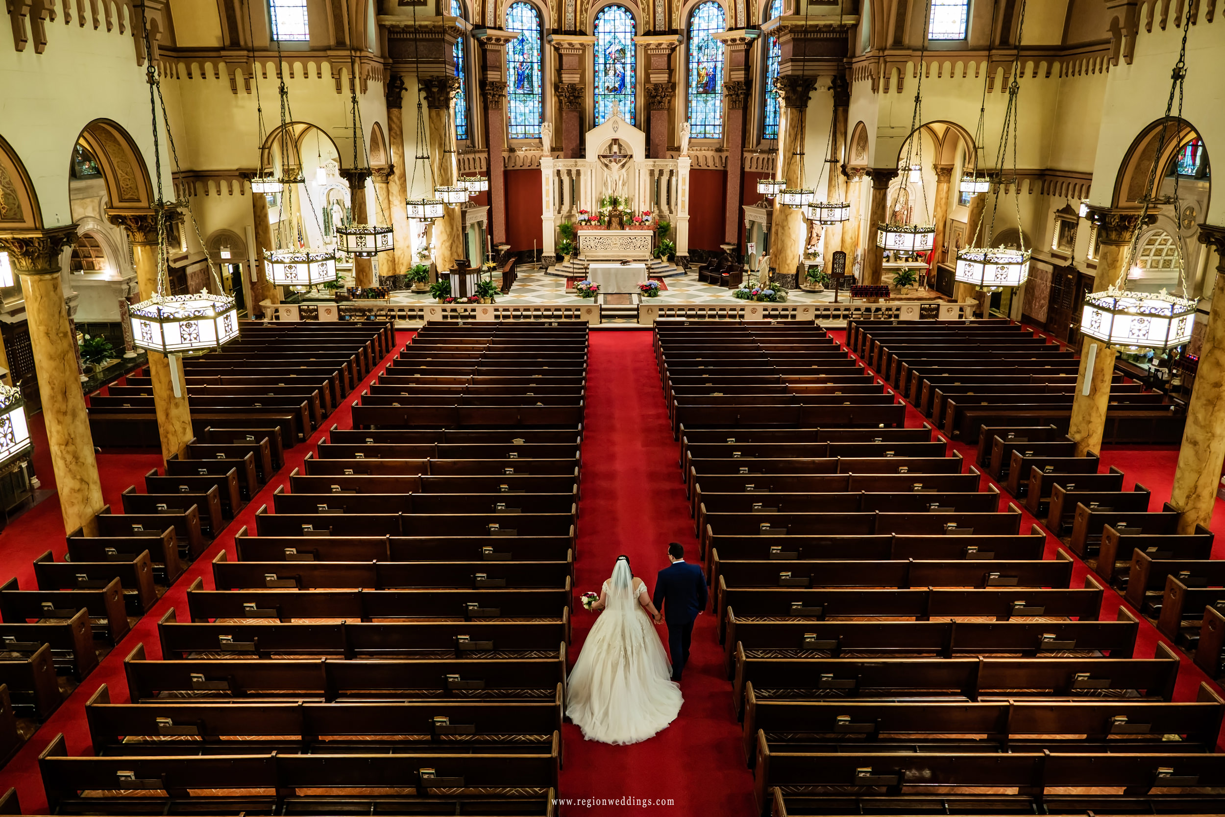 Bride and groom walk the center aisle at St. Andrew the Apostle Church in Calumet City, Illinois.
