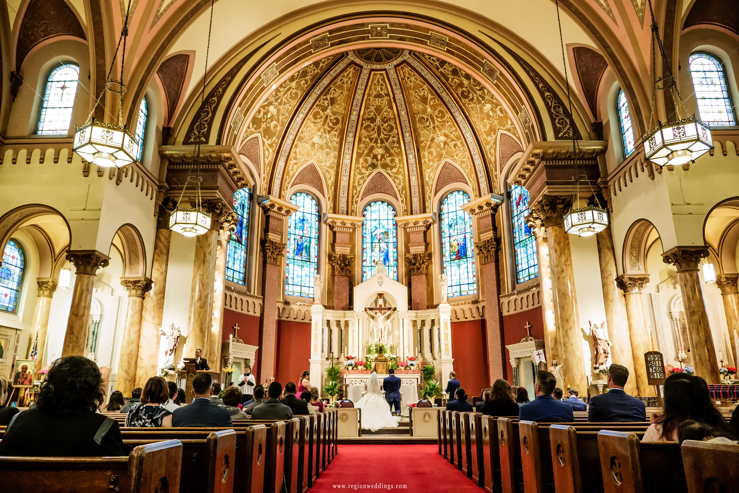 A view from the center aisle during a Chicago wedding ceremony at Saint Andrew The Apostle Church.