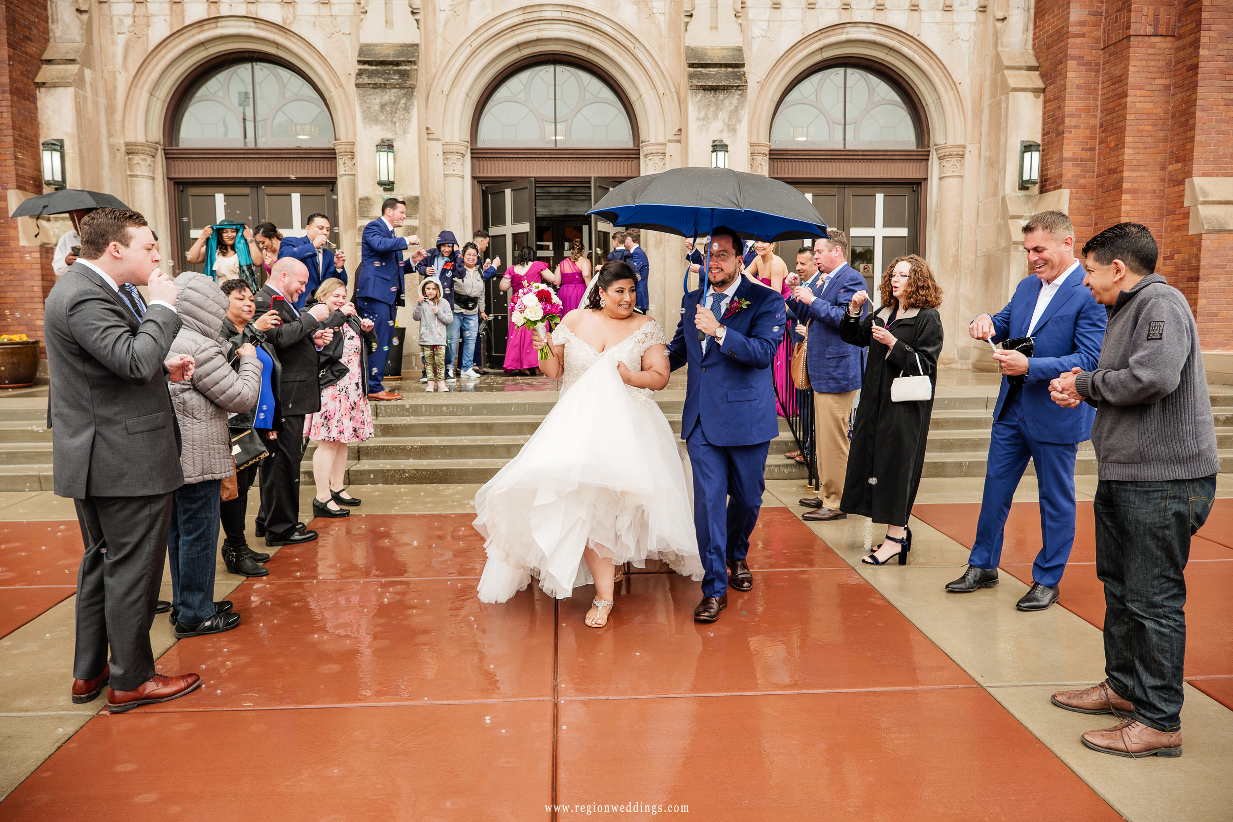 Bubbles and raindrops descend upon the bride and groom during their church wedding exit.