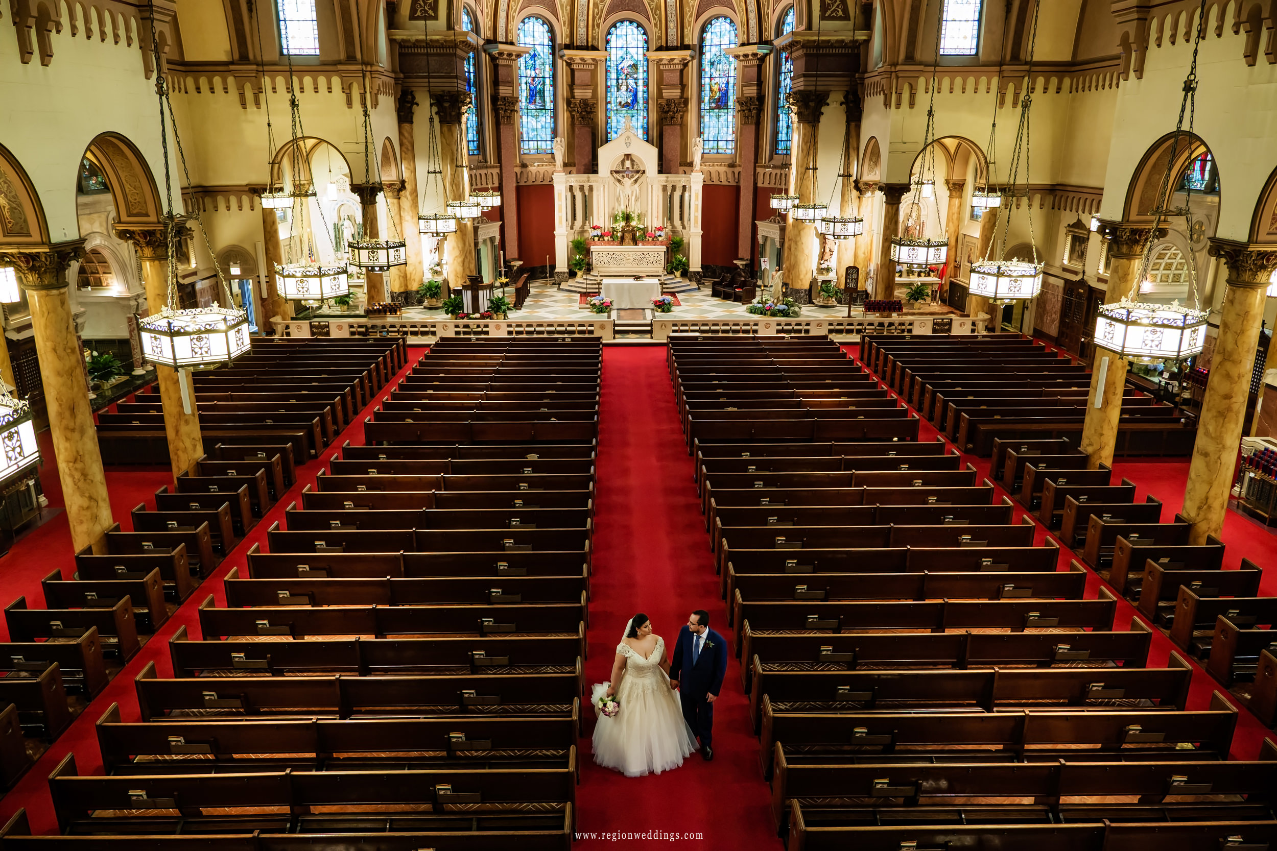 Bride and groom walk toward the church exit of Saint Andrew The Apostle Church.
