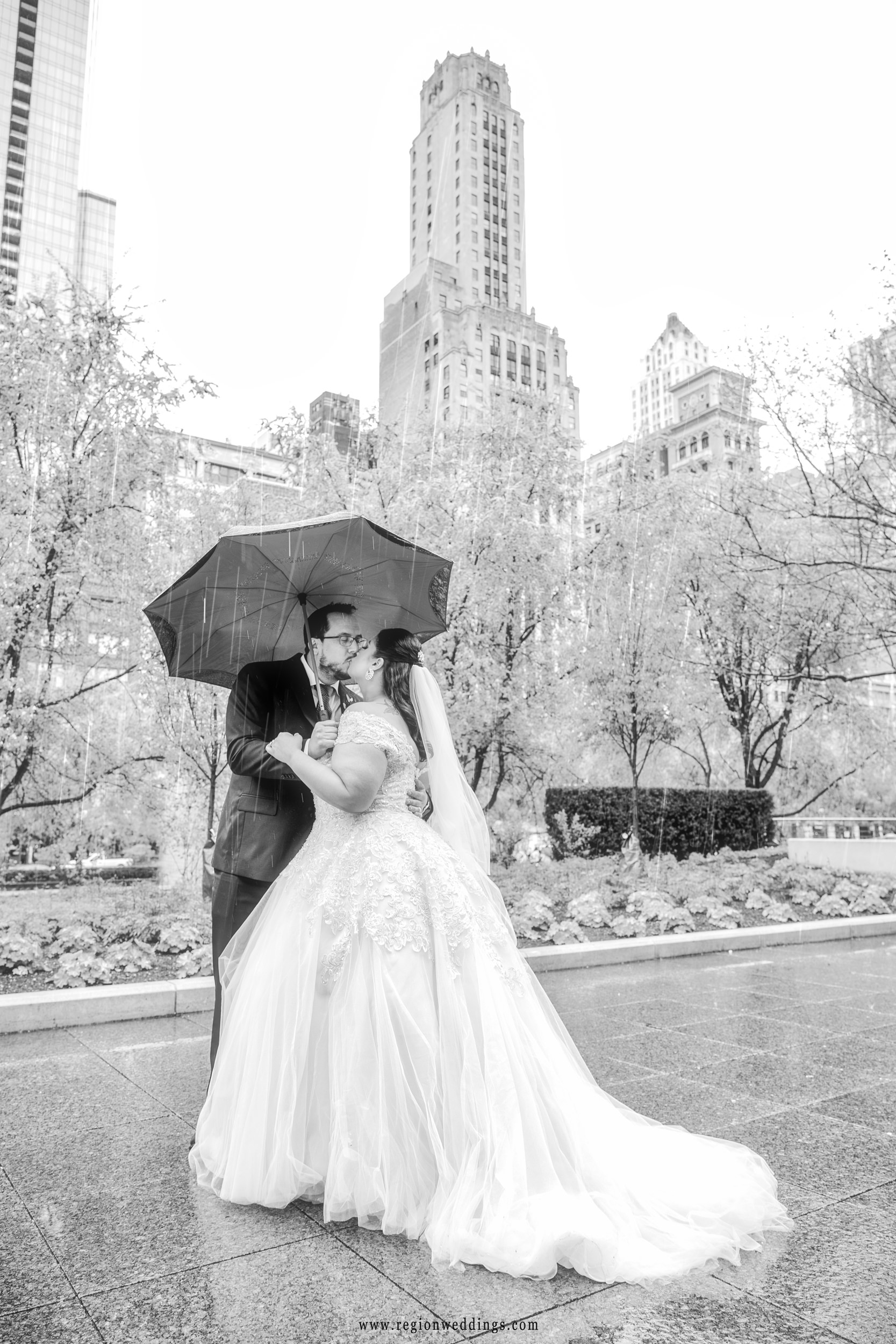 Bride and groom kiss under an umbrella as rain falls in downtown Chicago.