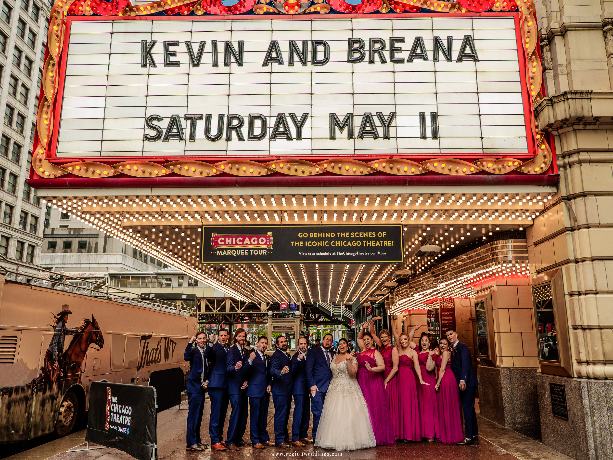 Wedding party group photo underneath the marquee of the Chicago Theater.