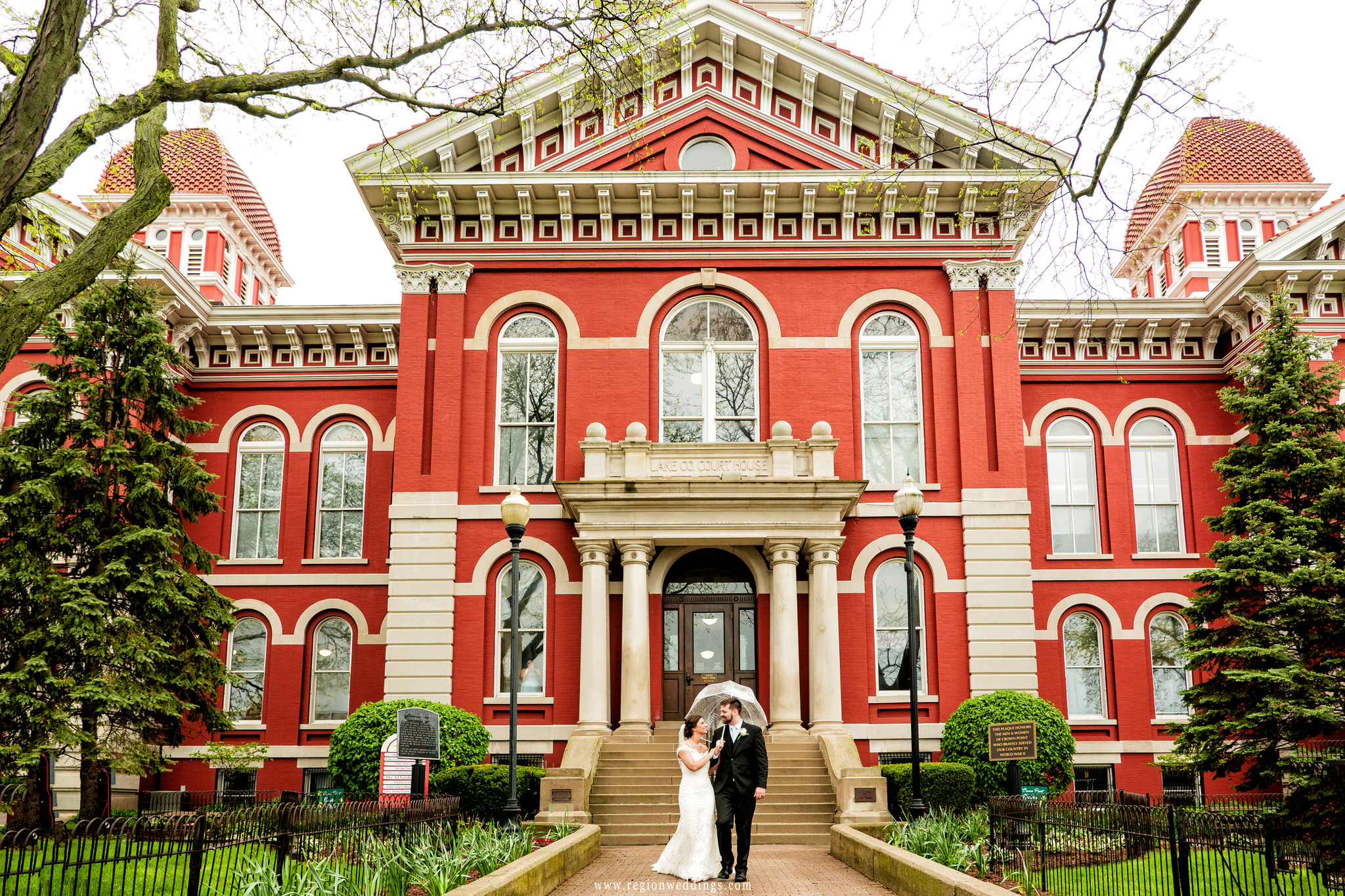 Newlyweds take a walk in the rain in front of the Old Crown Point Courthouse.
