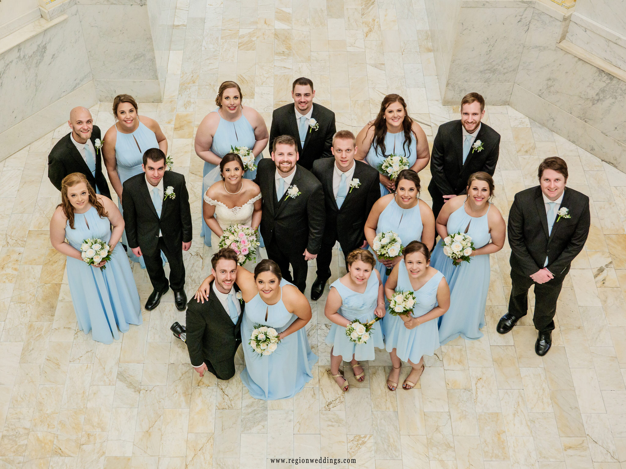 Wedding party group photo on the marble floor of Old Crown Point Courthouse.