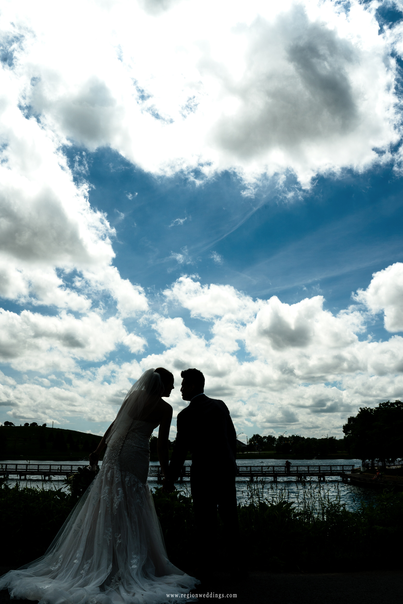 Blue sky silhouette of the bride and groom at Centennial Park in Munster, Indiana.