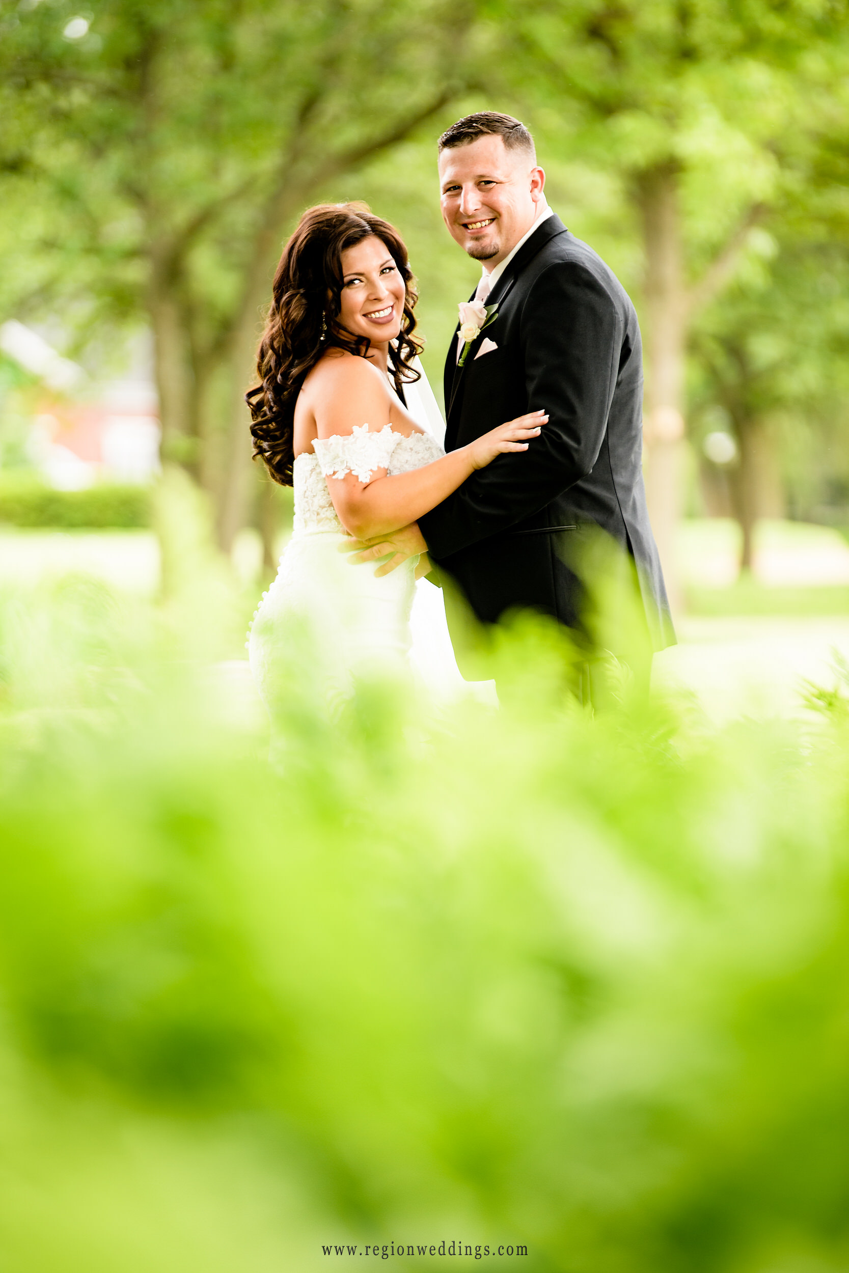 Bride and groom among the greenery of Briar Ridge Country Club.