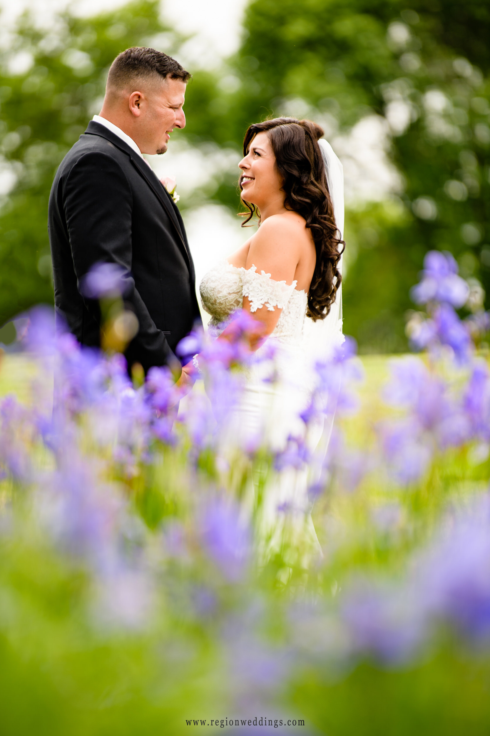 Loving eyes of the bride and groom with purple flowers in the foreground.