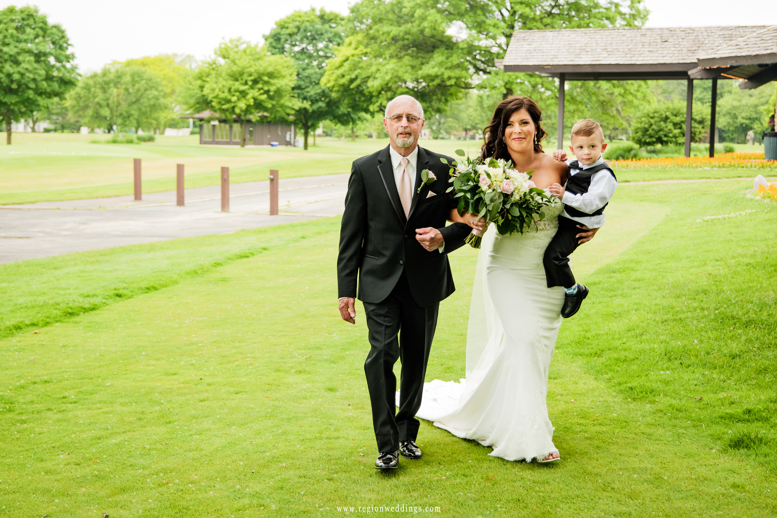 The bride makes her ceremony entrance alongside her father and son.