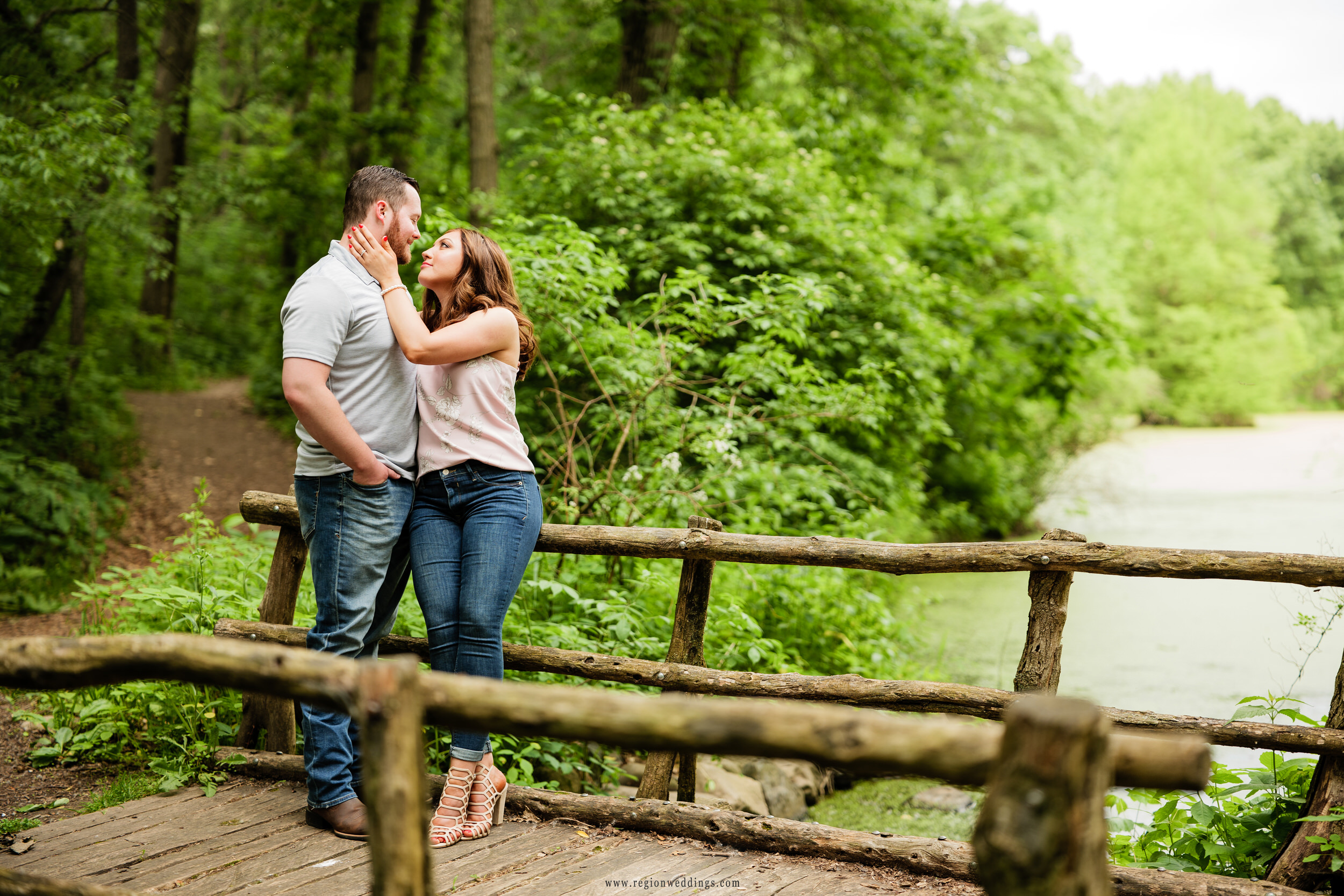 A romantic moment on a bridge surrounded by nature.