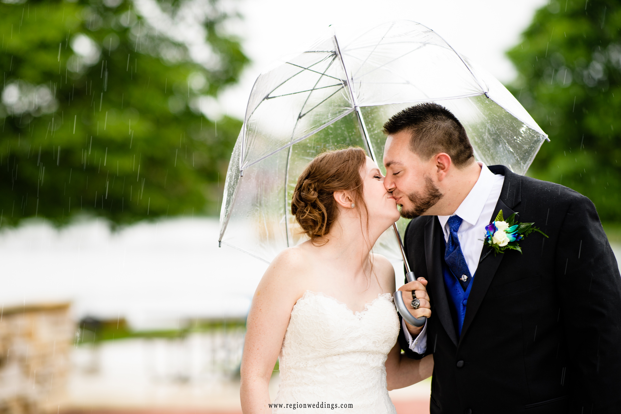 Bride and groom kiss under an umbrella at Centennial Park in Munster, Indiana.