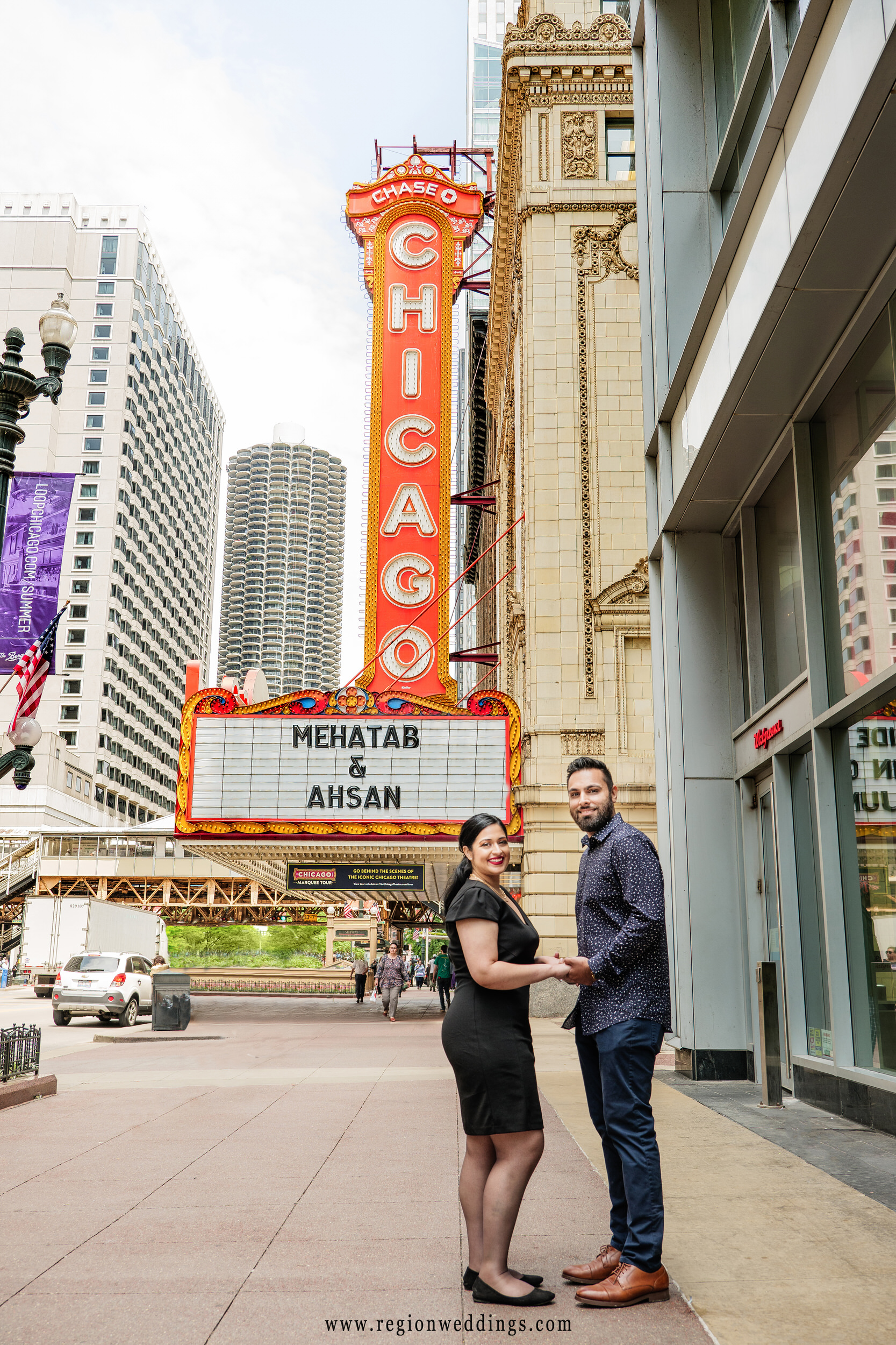 A couple poses in front of the Chicago Theater for their engagement photo session.