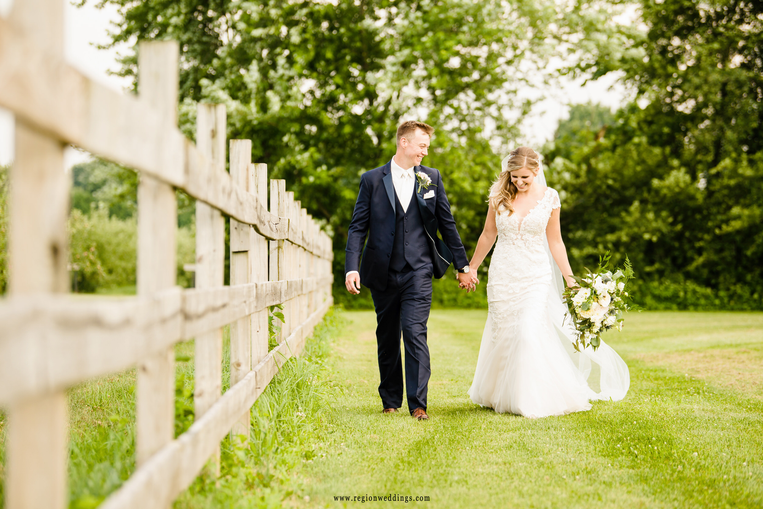 Bride and groom take a joyful walk in the fields at County Line Orchard.