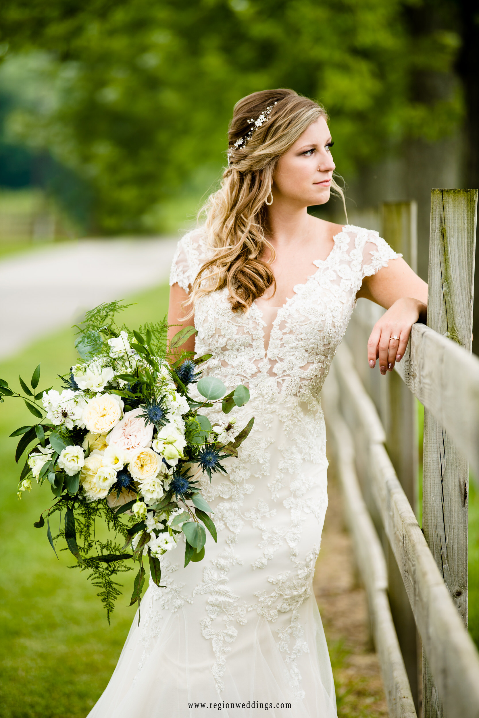The bride leans against a rustic fence on the grounds at County Line Orchard.