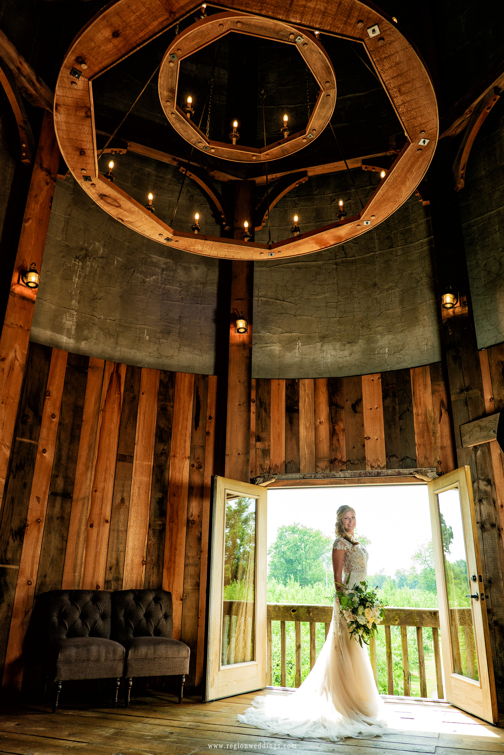 A lighted chandelier towers over the bride inside the grain silo at County Line Orchard.