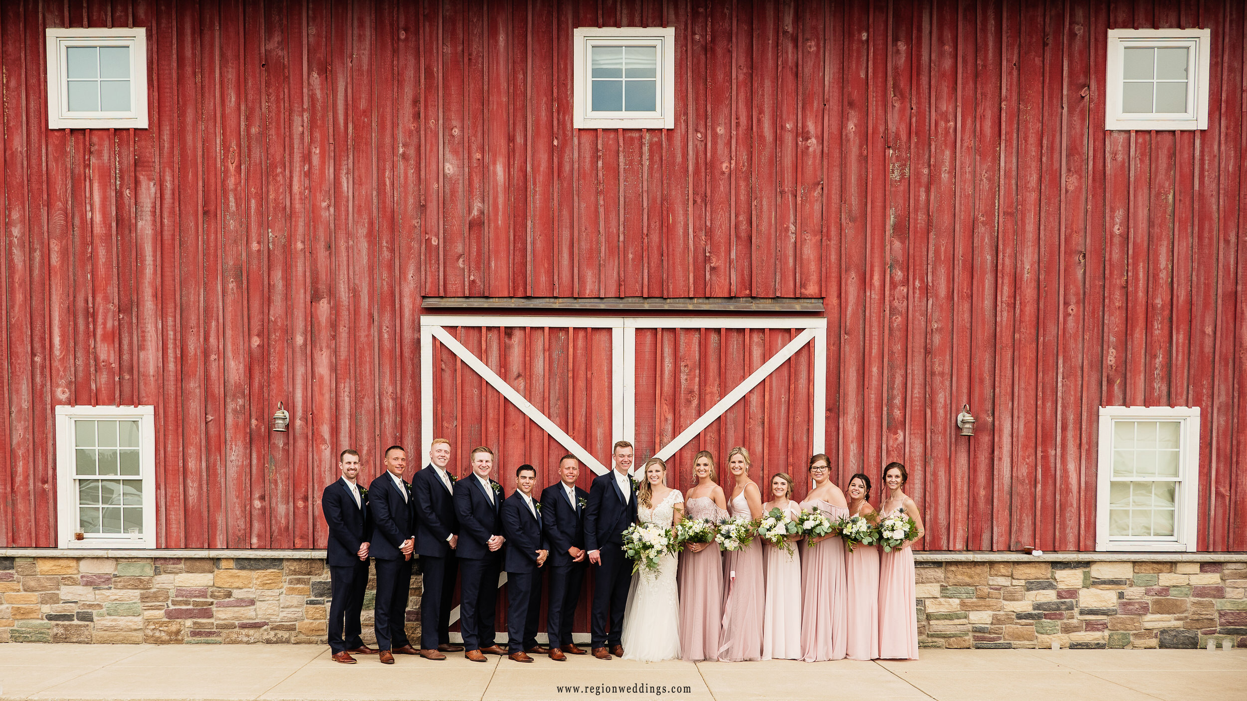 A wedding party group photo in front of the big red barn.