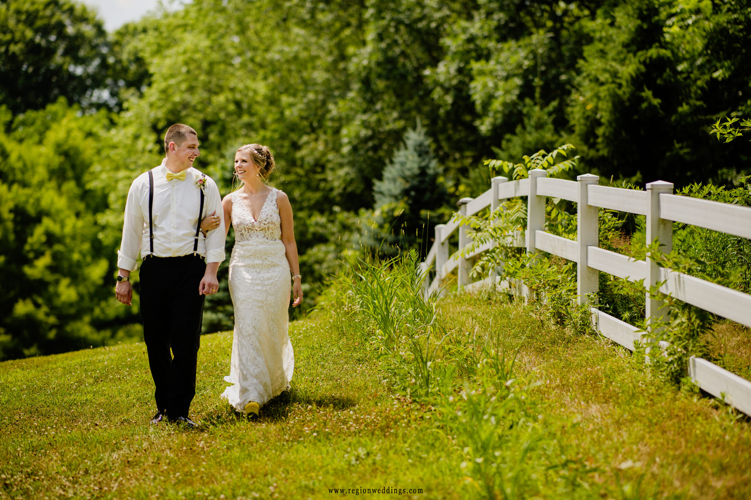 The bride and groom take a romantic stroll along the white picket fence at Heston Hills.